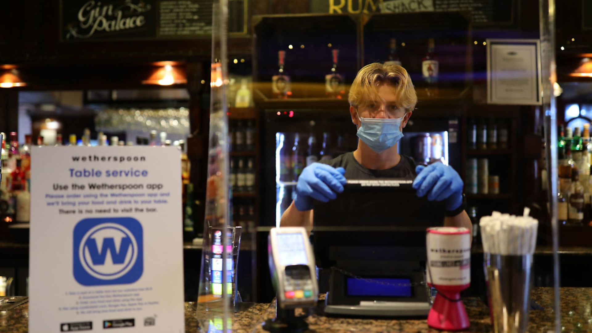 A member of staff in PPE waits to serve drinkers at the reopening of a Wetherspoons pub. Photograph: Aaron Chown/PA Wire. - Credit: PA