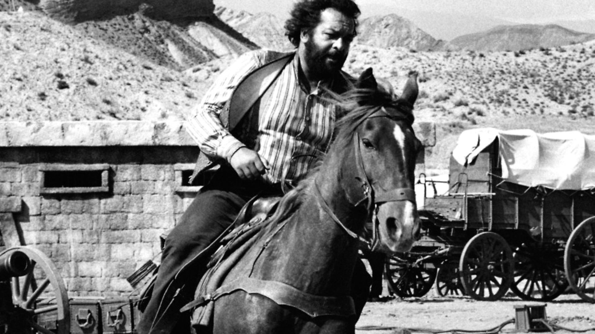 Italian actor and swimmer Bud Spencer (Carlo Pedersoli) riding a horse in the film A Reason to Live. 1972 (Photo by Mondadori Portfolio by Getty Images) - Credit: Mondadori via Getty Images