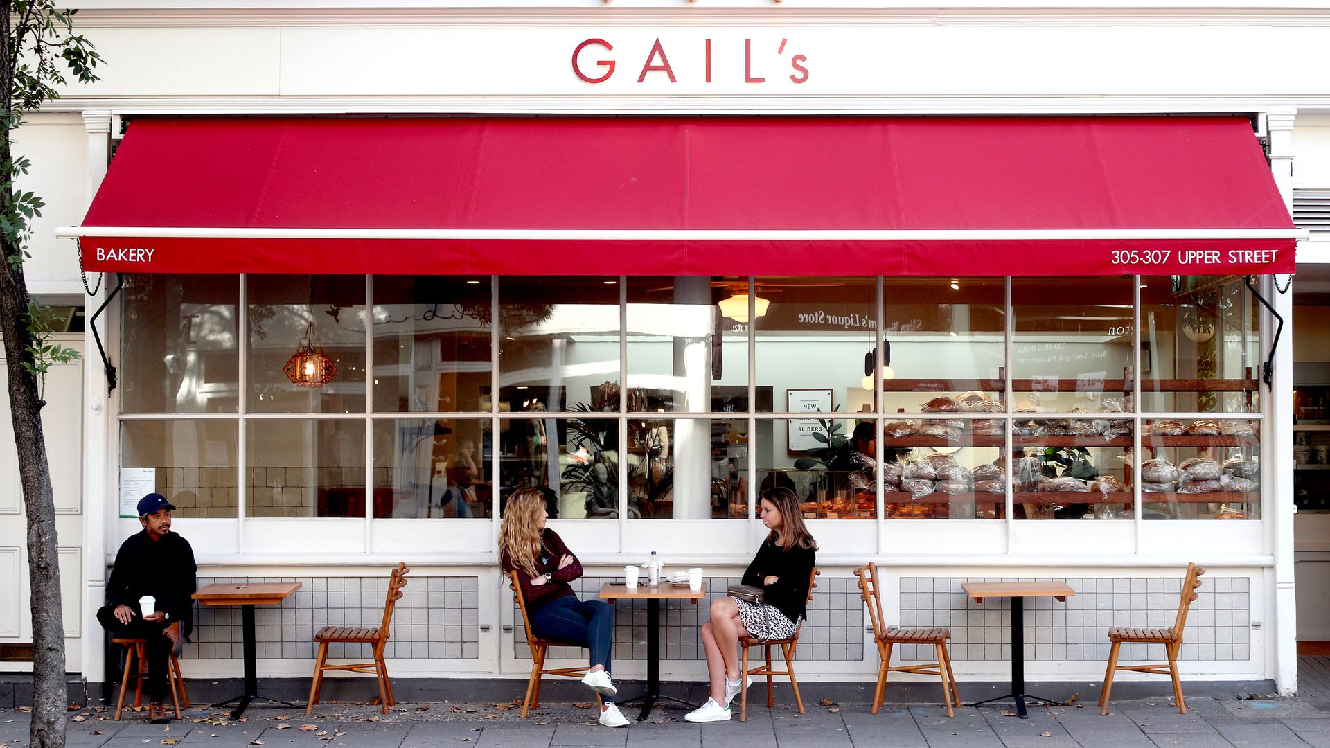 Customers observe social distancing as they sit outside a branch of Gail's bakery. - Credit: PA