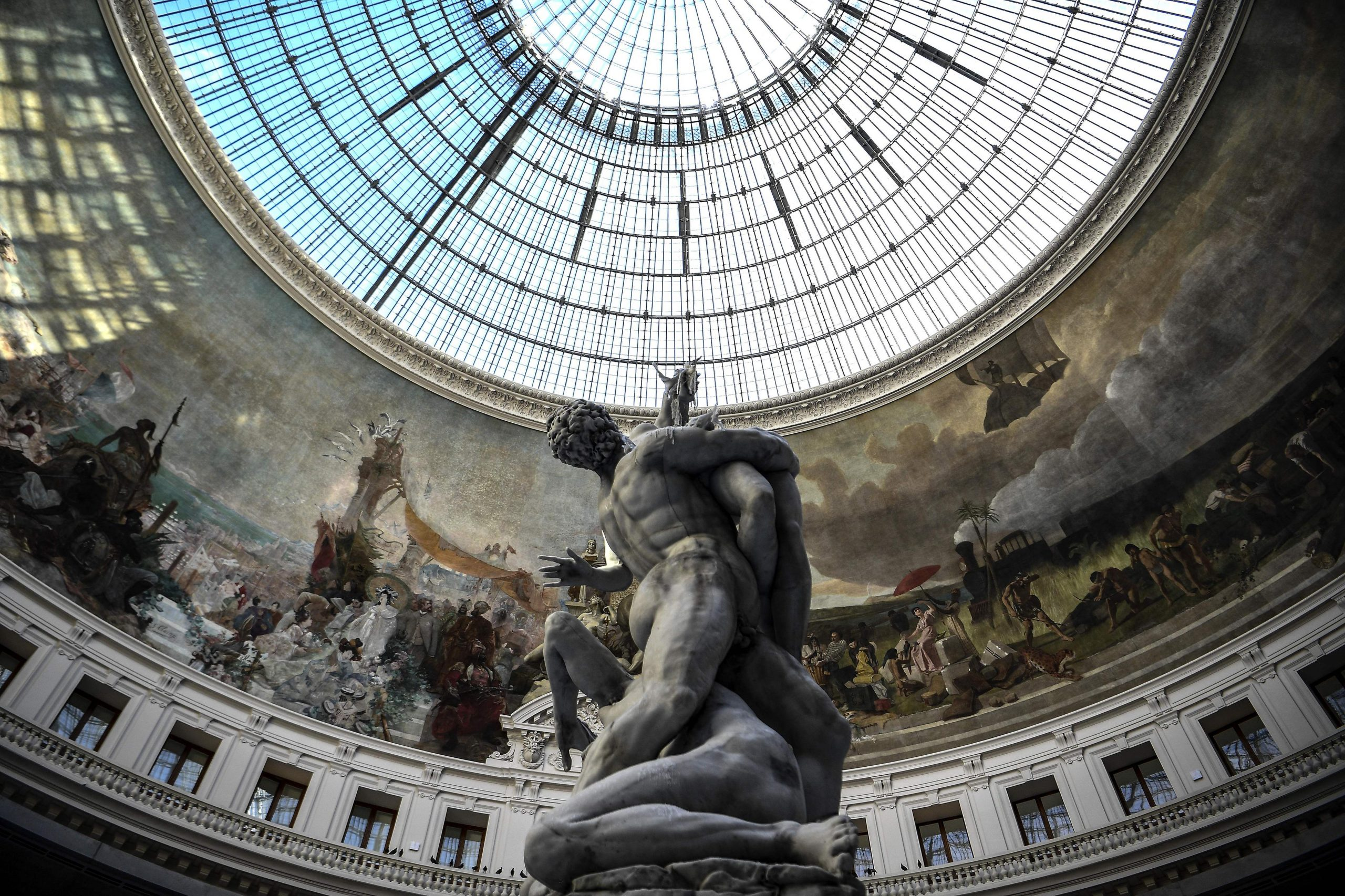 """A picture taken on May 22, 2021 shows a partially-melted wax sculpture by Swiss artist Urs Fischer, depicting a replica of the marble sculpture by Italian artist Giambologna """"The Rape of the Sabine Women"""", after its wick was lit at the Bourse de Commerce-Pinault Collection, which houses French billionaire Francois Pinault's private art collection in Paris."""