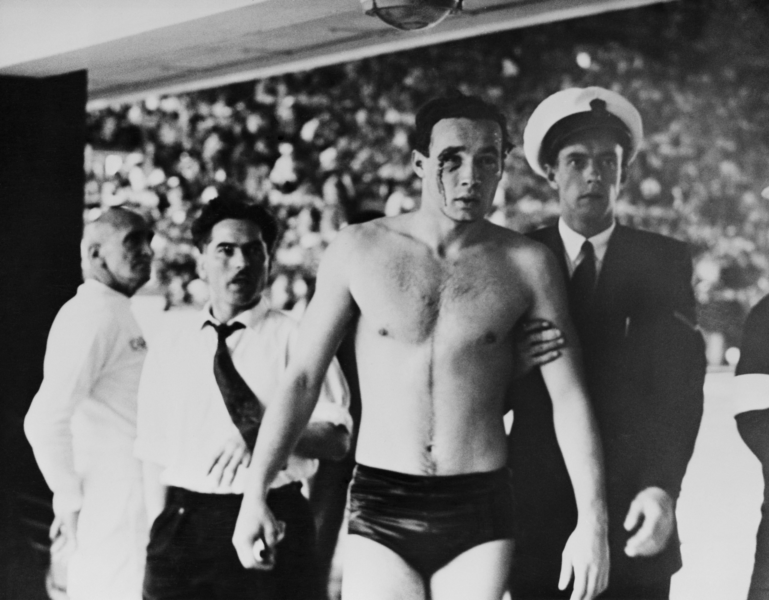 Ervin Zador is escorted from the pool, with blood pouring from a wound inflicted by a Russian opponent.