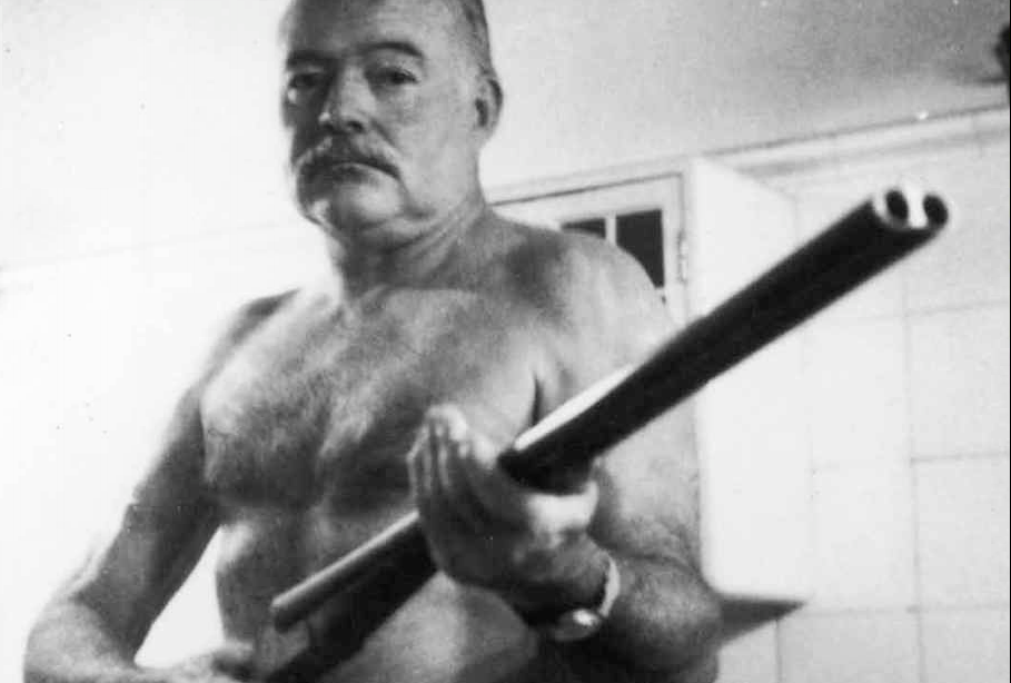 Ernest Hemingway, posing in 1952 with the Scott double-barrelled duck-hunting shotgun he - most likely - used to kill himself almost ten years later