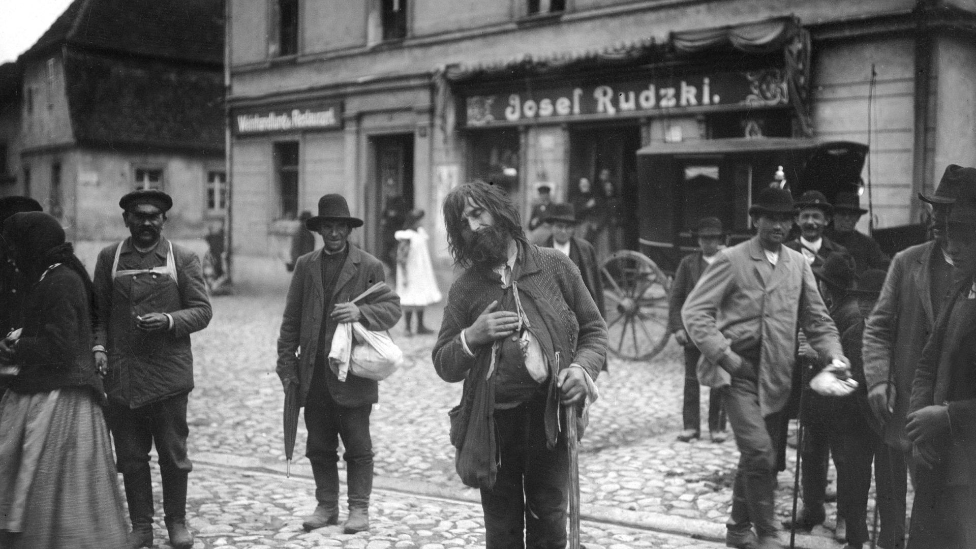 Locals stare at a beggar in the street in Posen, Prussia - now part of Poland - in a photograph from 1910 - Credit: ullstein bild via Getty Images