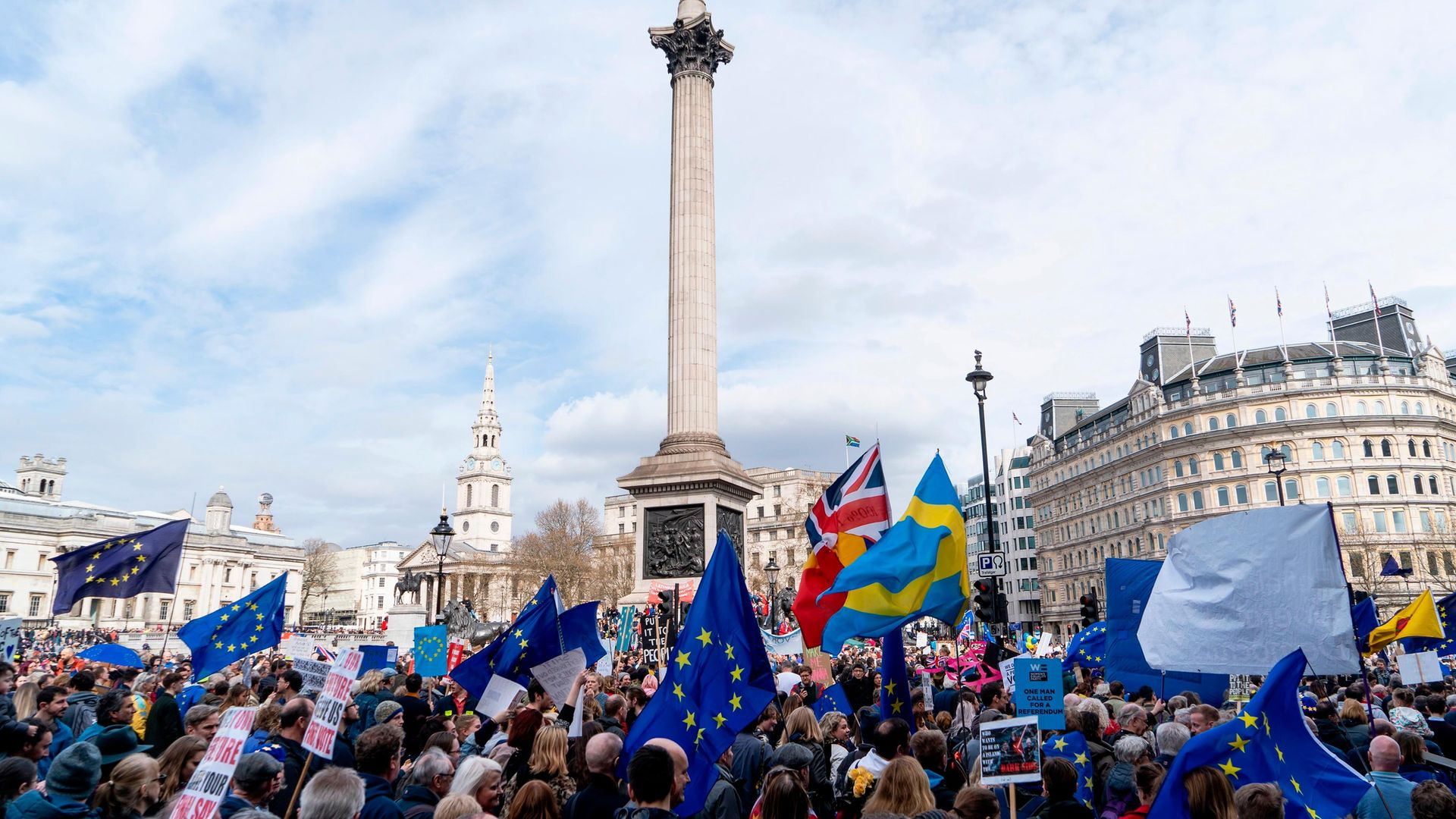 People hold up placards and European Union flags as they pass Trafalgar Square on a march and rally - Credit: NIKLAS HALLE'N/AFP via Getty Images