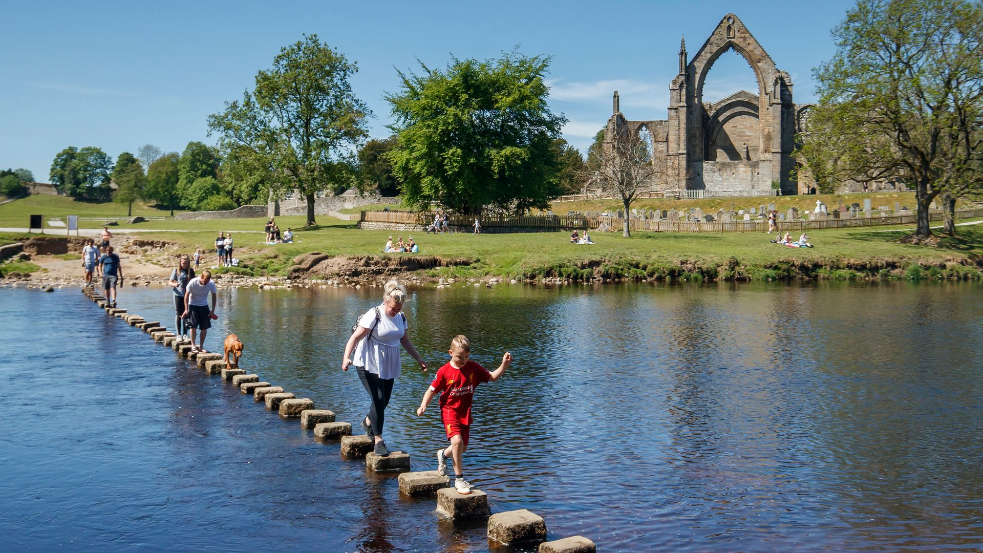 People enjoy the weather at Bolton Abbey in North Yorkshire as people flocked to parks and beaches after the first lockdown measures eased - Credit: PA