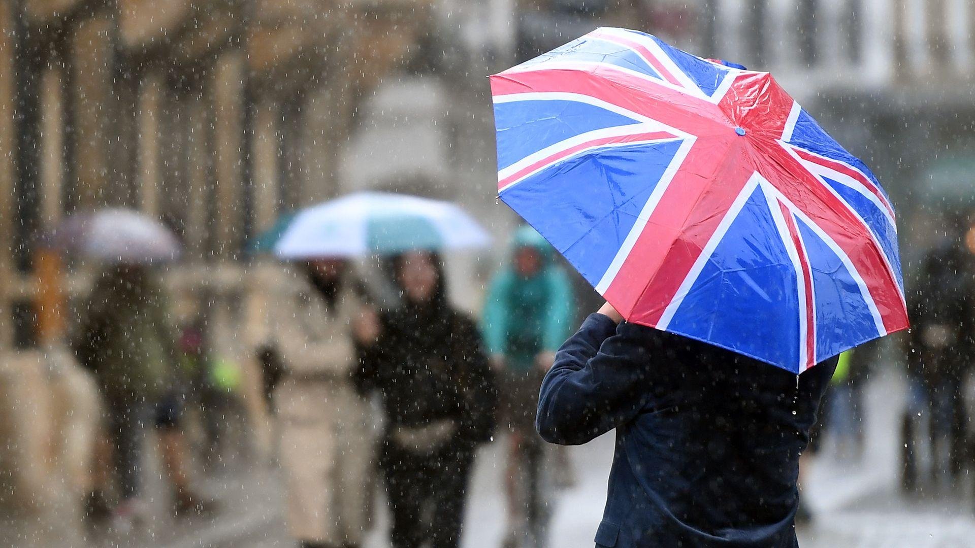 A man carries a Union flag umbrella - Credit: PA