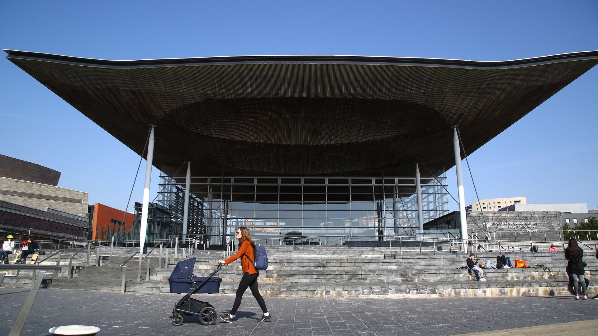 A woman pushes a pram past the senedd building in Cardiff Bay - Credit: AFP via Getty Images