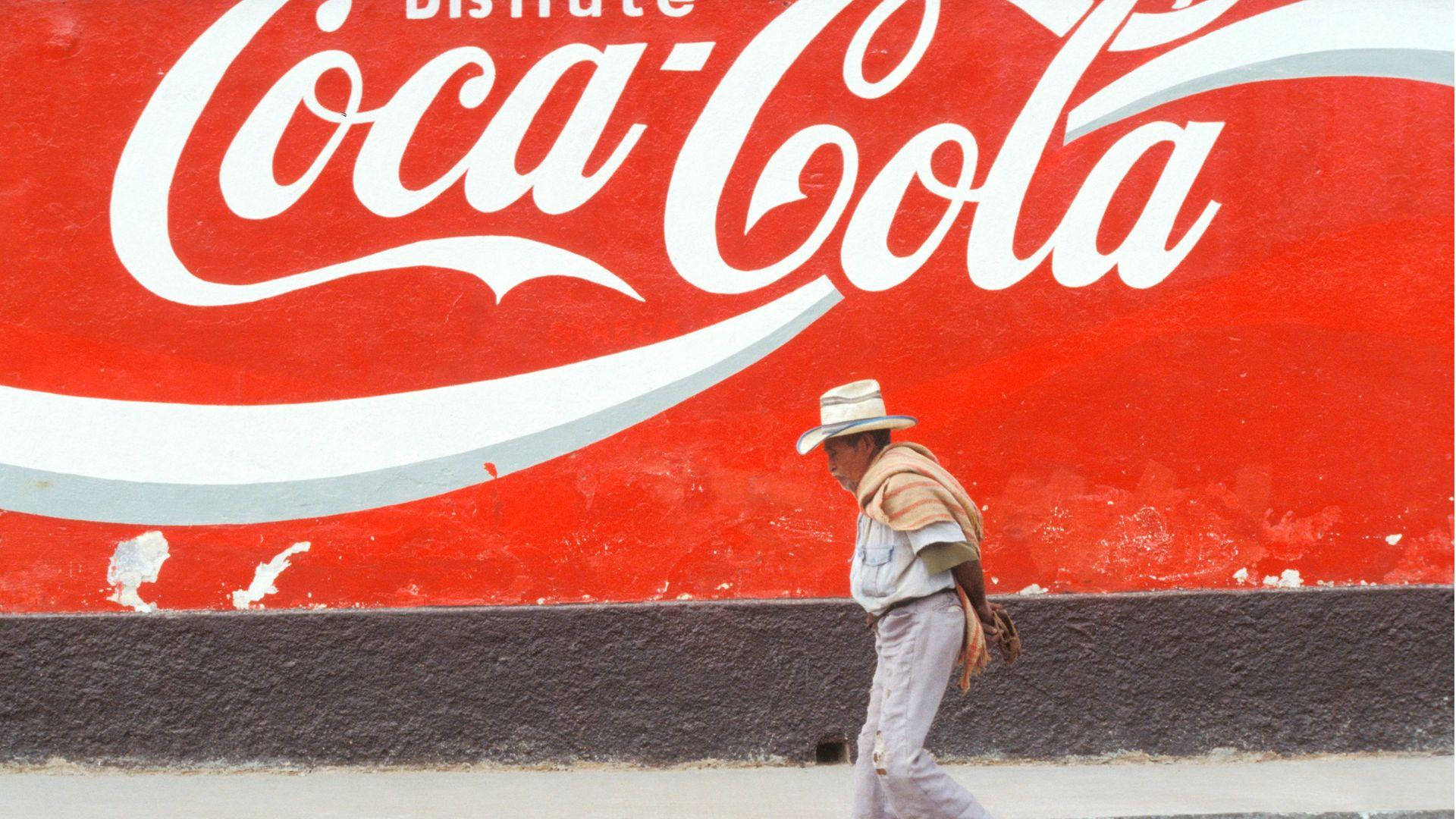 A man walks past a Coca-Cola advert in San Cristobal de las Casas, Mexico - Credit: Riccardo Lombardo/Reda&Co/Universal Images Group via Getty Images