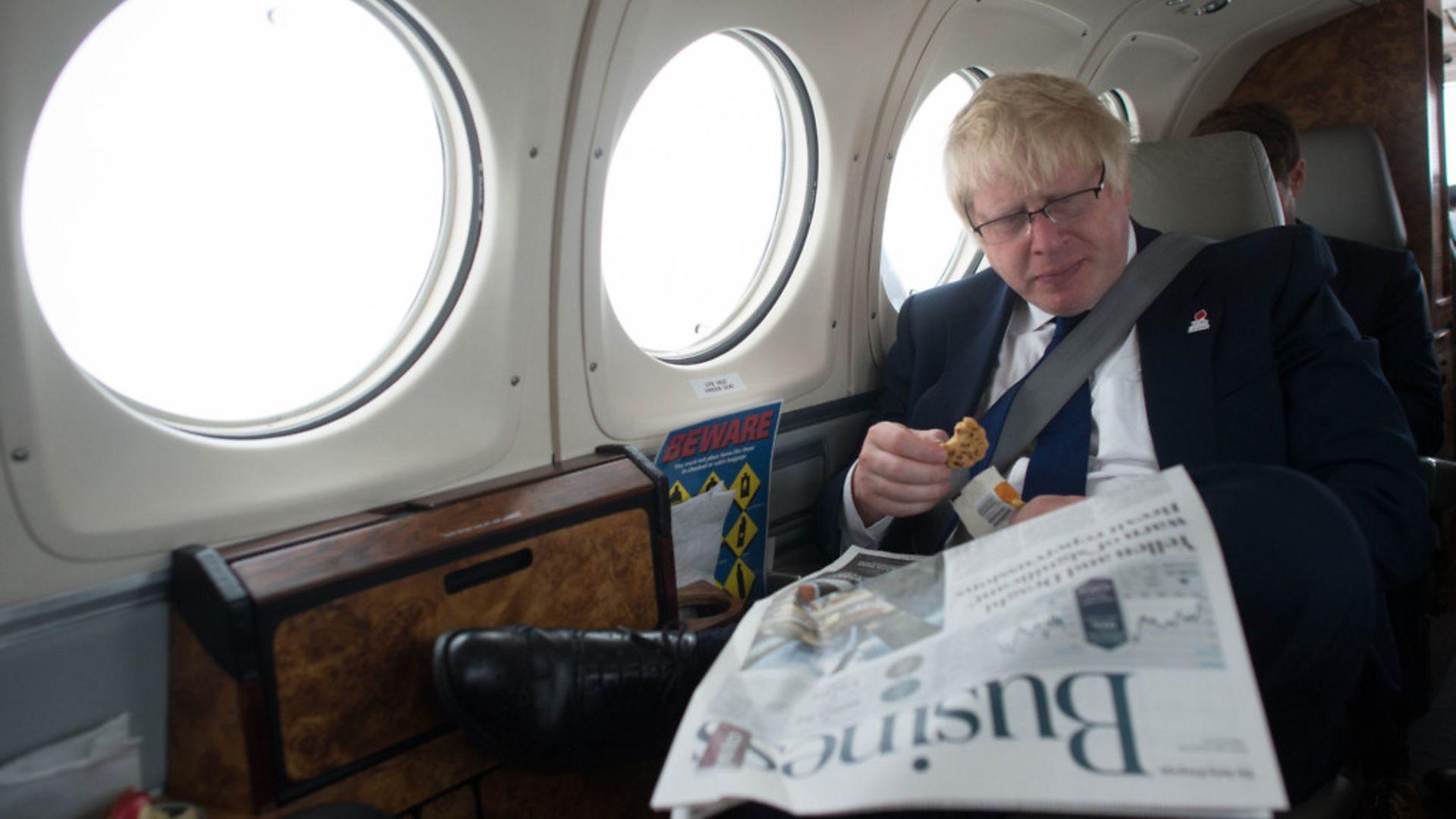 Boris Johnson reads a newspaper on a plane - Credit: Stefan Rousseau/PA