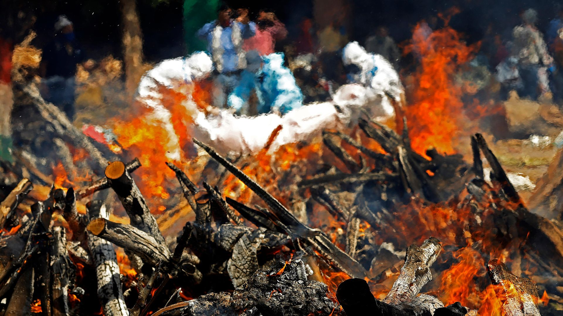 Undertakers wearing protective suits carry a body next to a burning pyre of a Covid victims in Delhi - Credit: SOPA Images/LightRocket via Gett