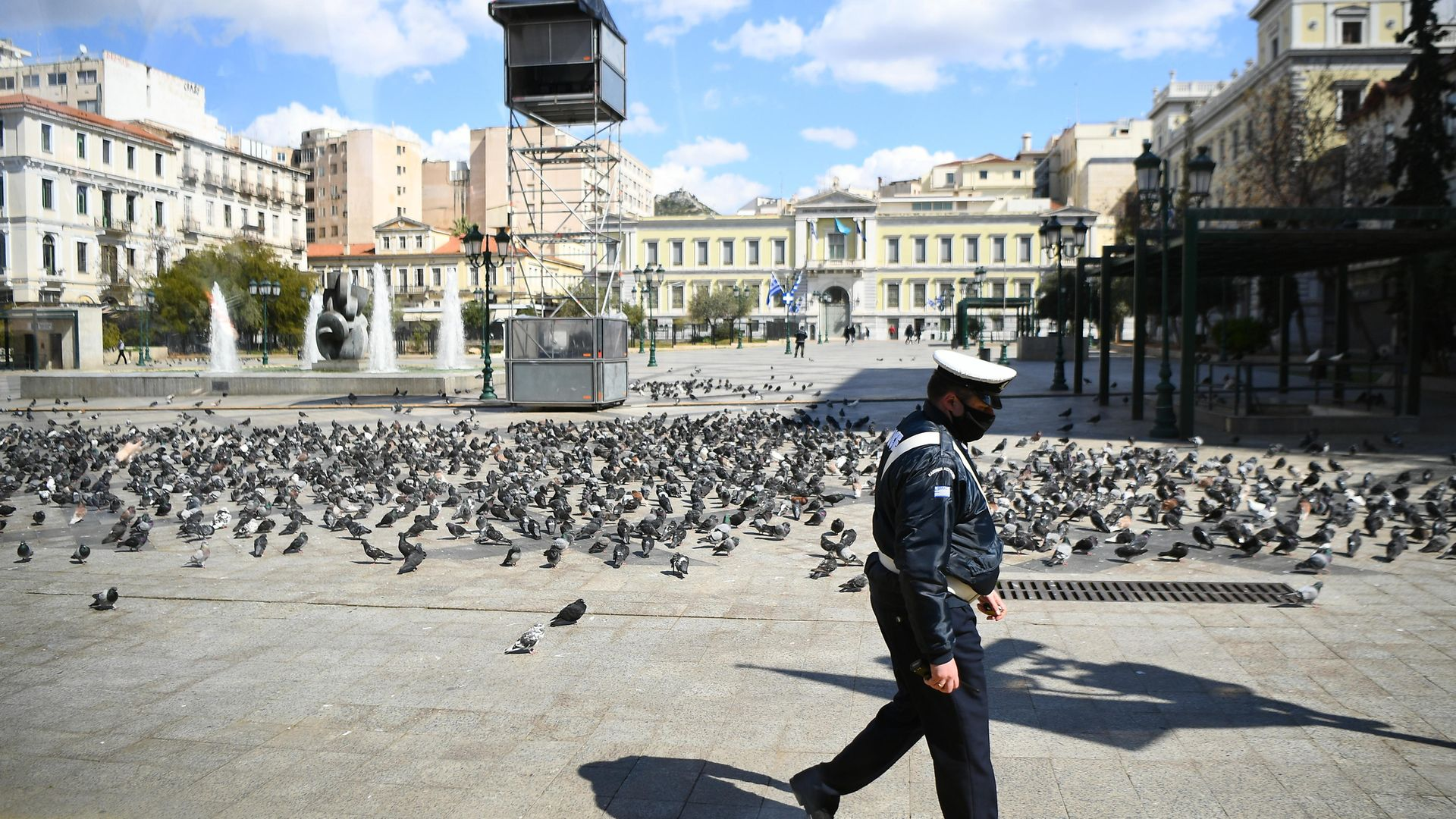 A police officer walks past an empty square in the centre of Athens, Greece, during lockdown - Credit: PA