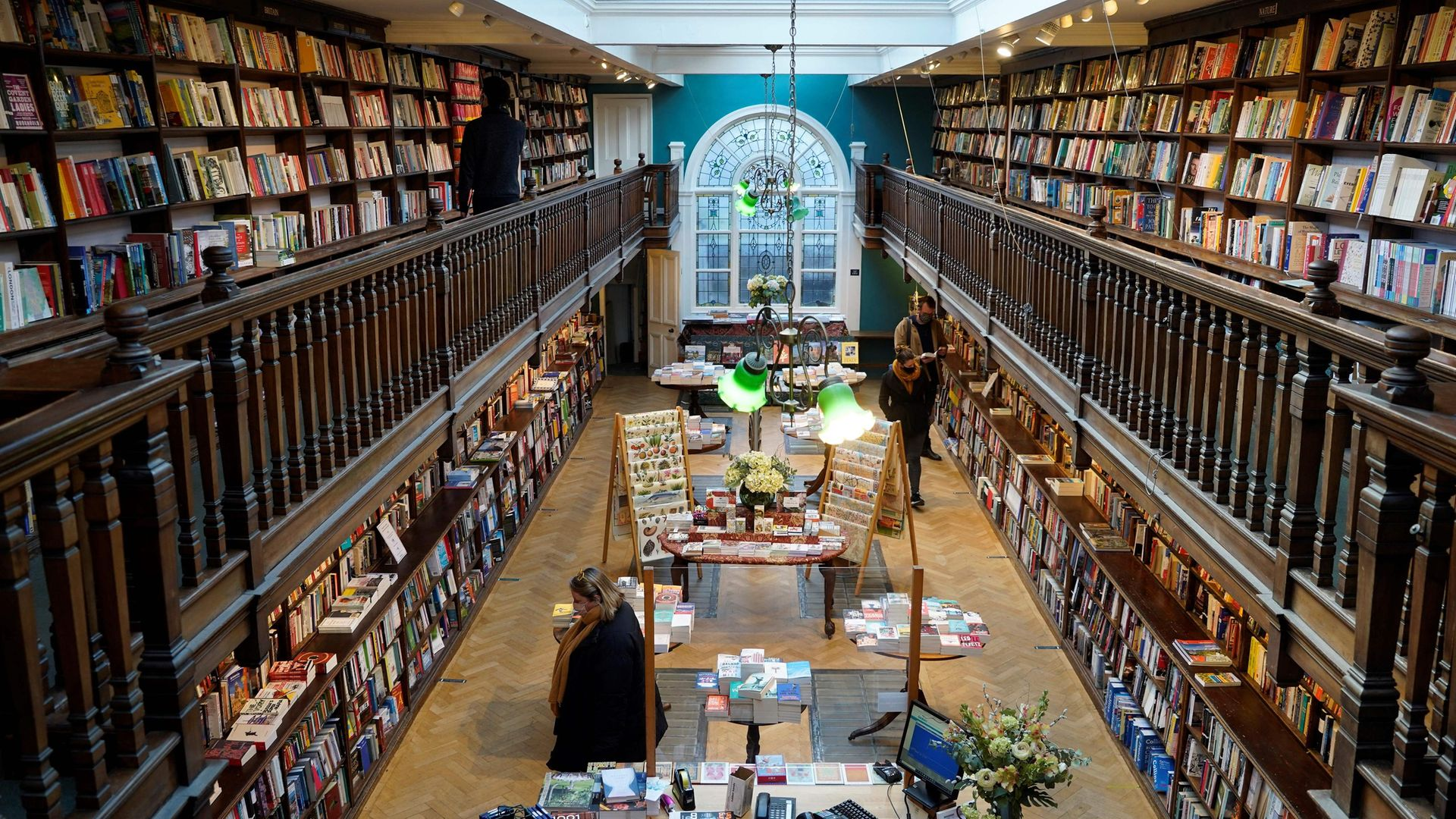 Customers wearing face masks browse for books inside the re-opened Daunt Books independent bookshop in London, after the easing of lockdown - Credit: AFP via Getty Images
