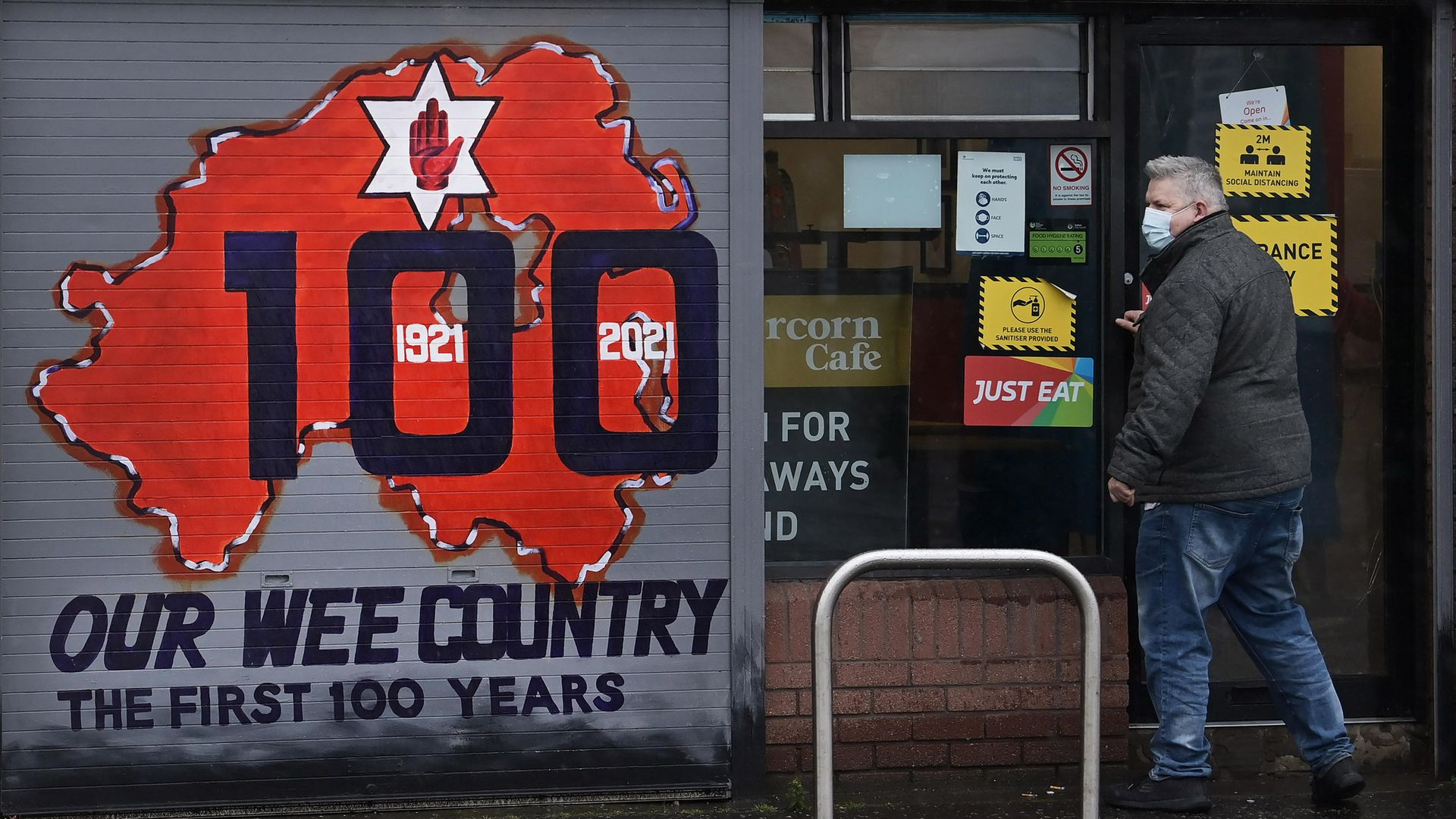 A freshly painted mural on a Belfast shop front marks Northern Ireland's centenary - Credit: Getty Images