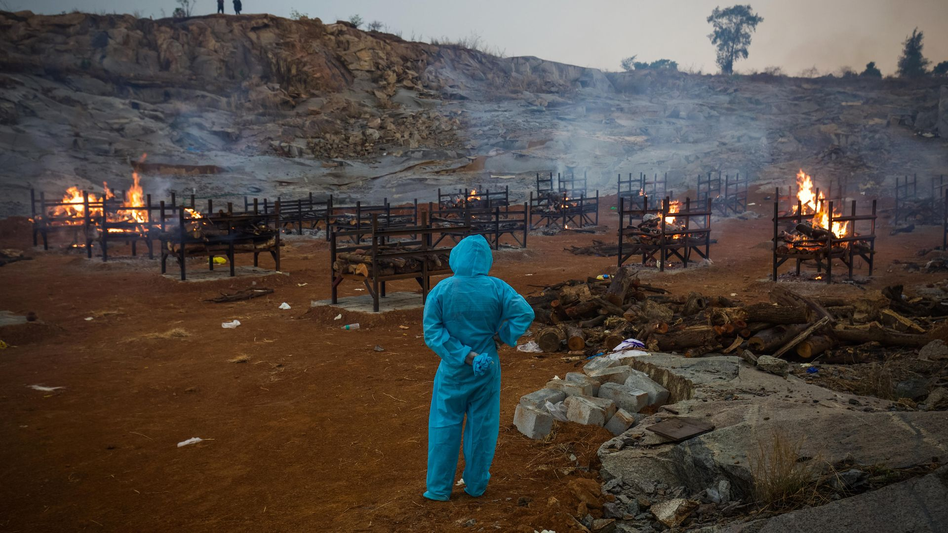 A man watches mass cremations in a disused granite quarry repurposed to cremate those who have died from Covid in Bengaluru, India - Credit: Getty Images