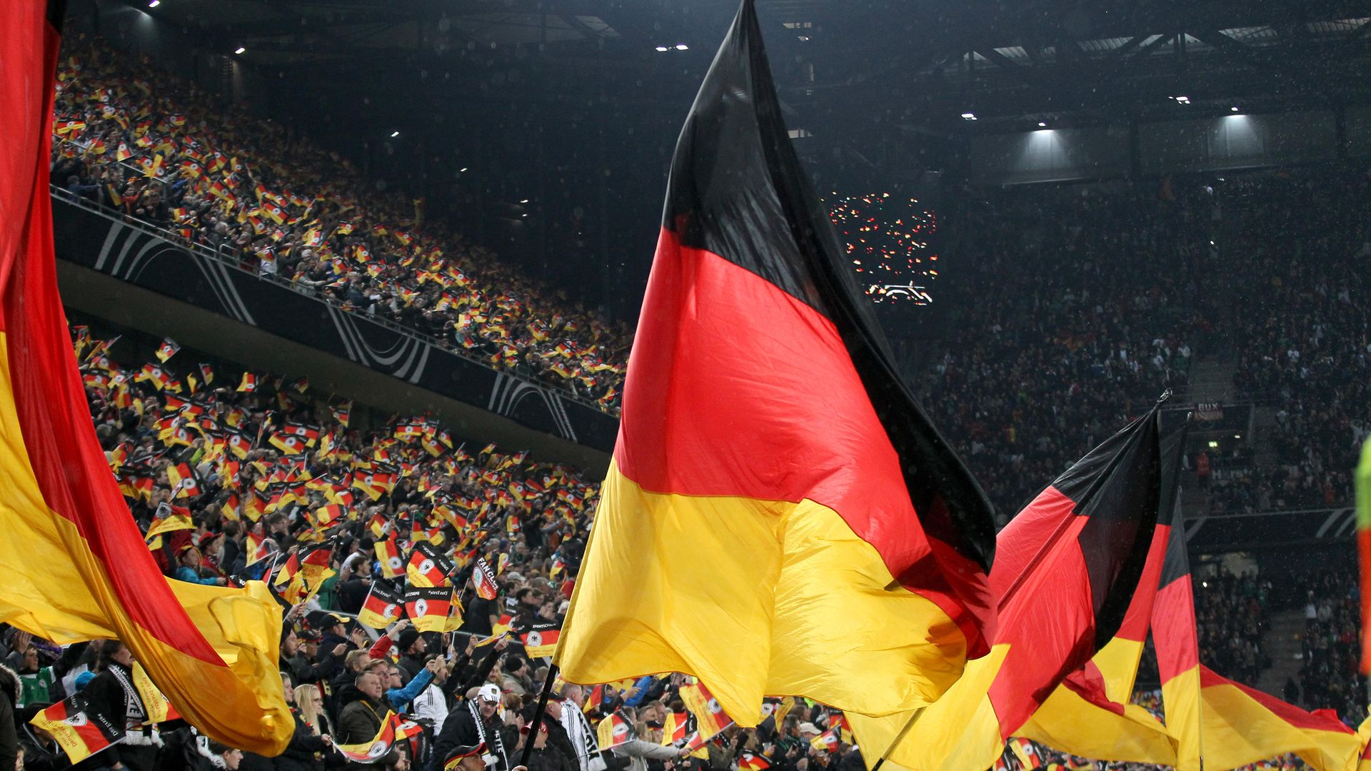 A German flag is flown in a sports stadium - Credit: PA