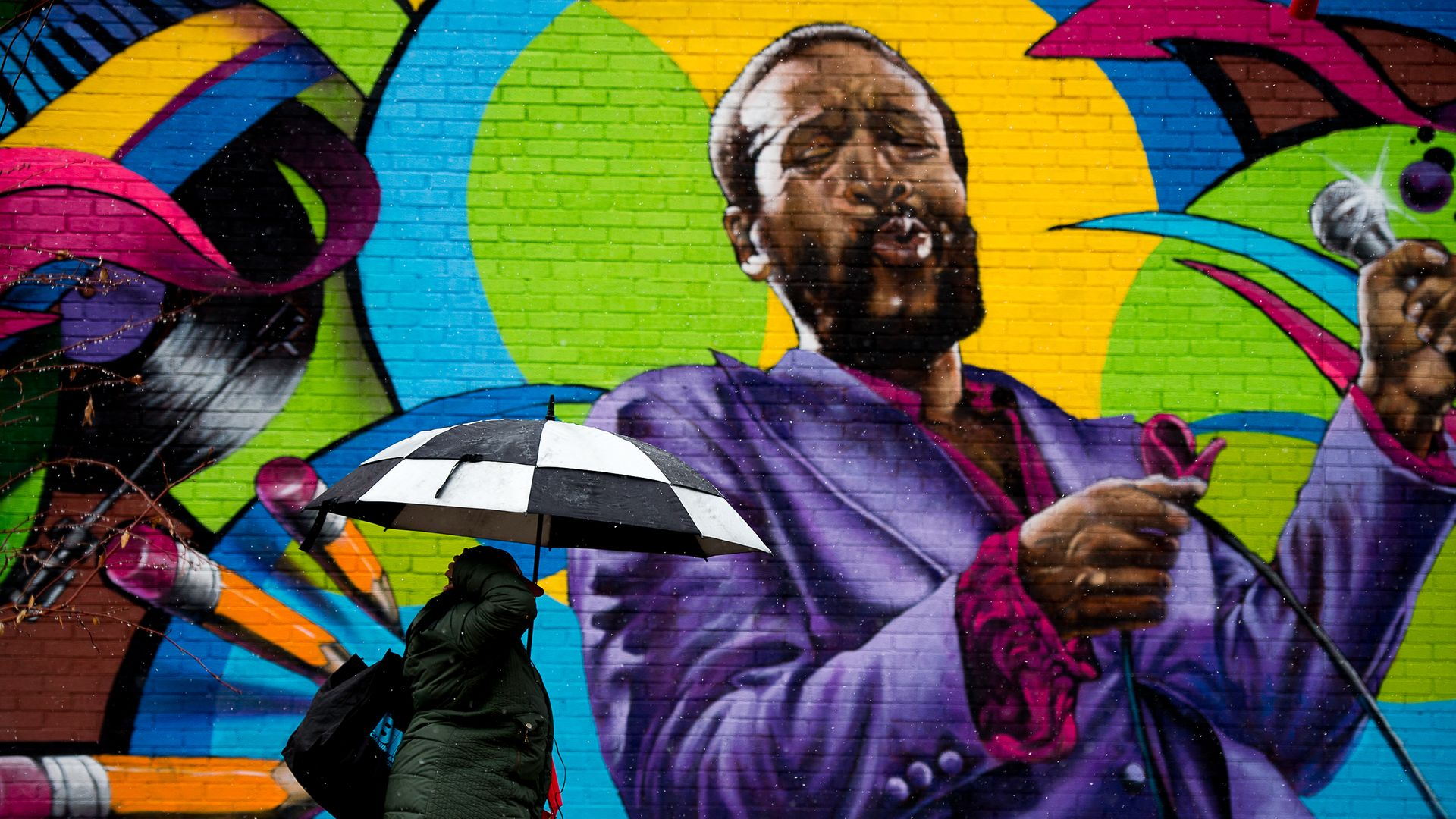 A woman walks past local artist Aniekan Udofia's mural of Marvin Gaye in Washington, DC - Credit: Photo by Andrew Harnik for The Washington Post via Getty Images