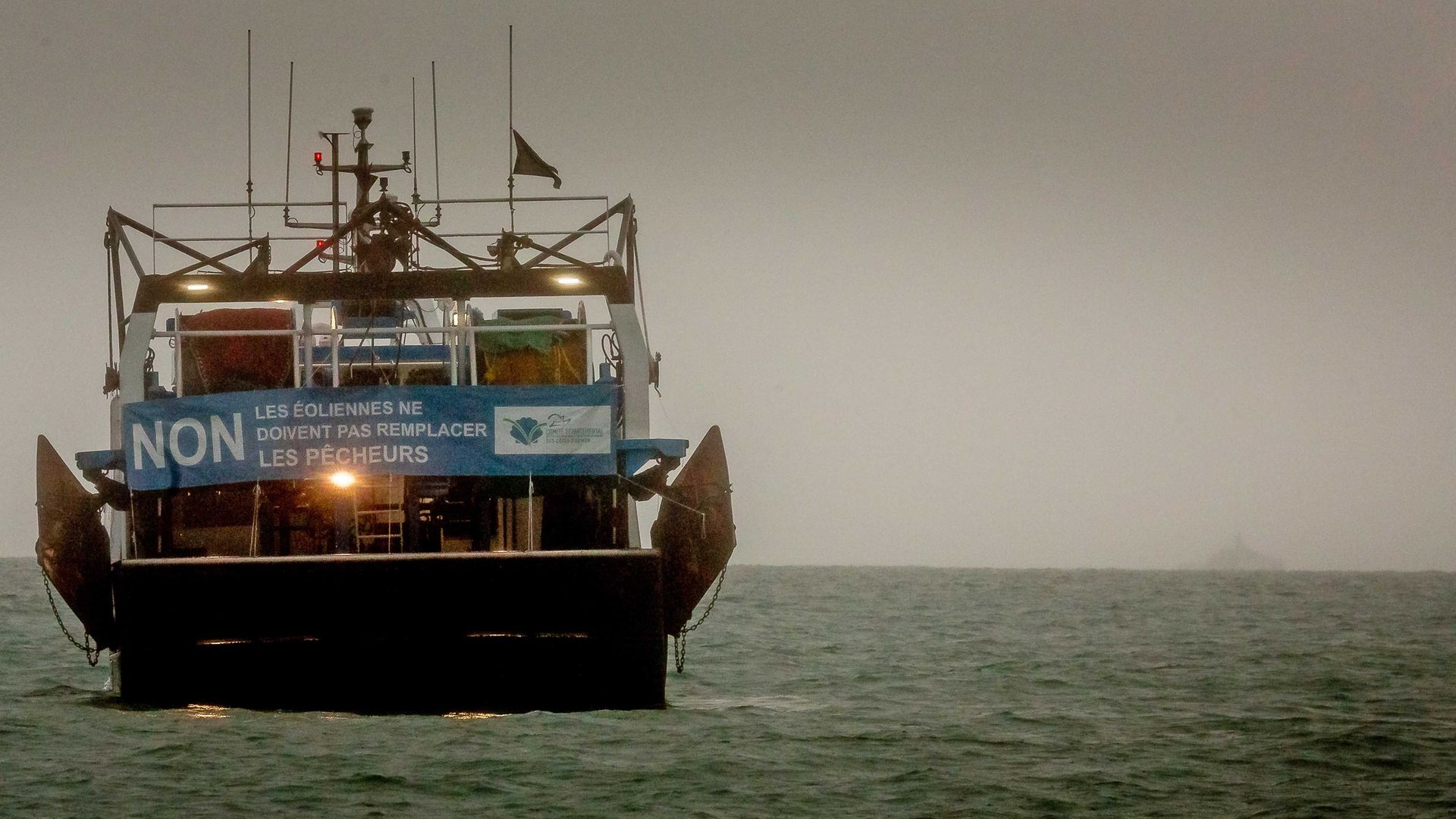 A French fishing boat with a protest sign opposing new fishing licenses in St Helier, Jersey - Credit: Getty Images