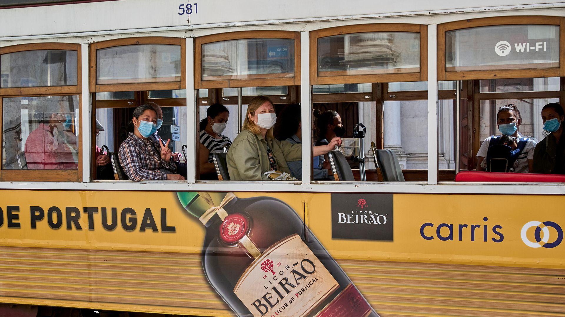 Mask-clad passengers ride a tram during the COVID-19 Coronavirus pandemic in Lisbon, April 2021  Photo by Horacio Villalobos/Corbis via Getty Images - Credit: Photo by Horacio Villalobos/Corbis via Getty Images