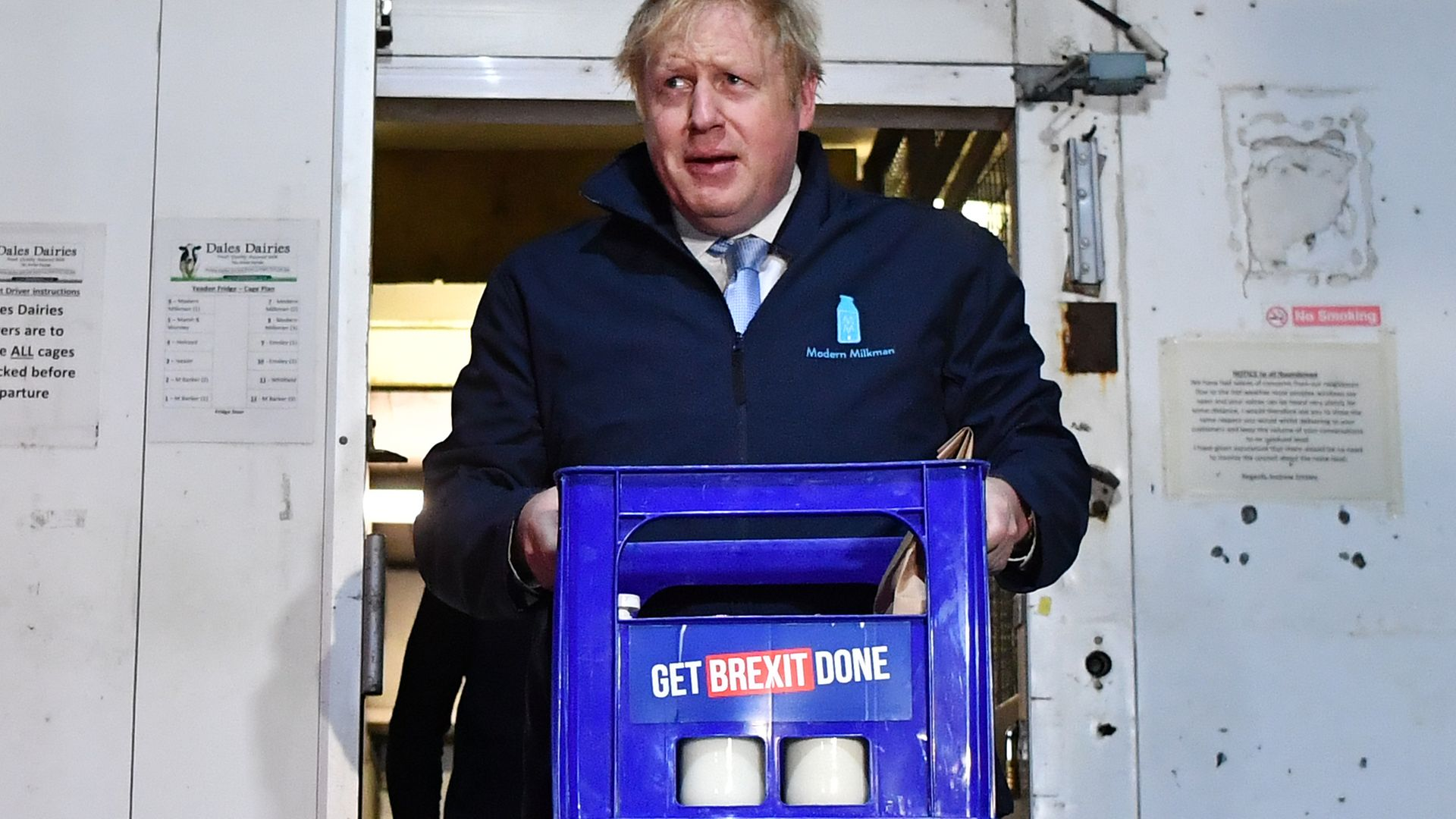 Boris Johnson carries a crate of milk on the final day of campaigning before the 2019 general election - Credit: Photo by Ben Stansall-WPA Pool/Getty Images