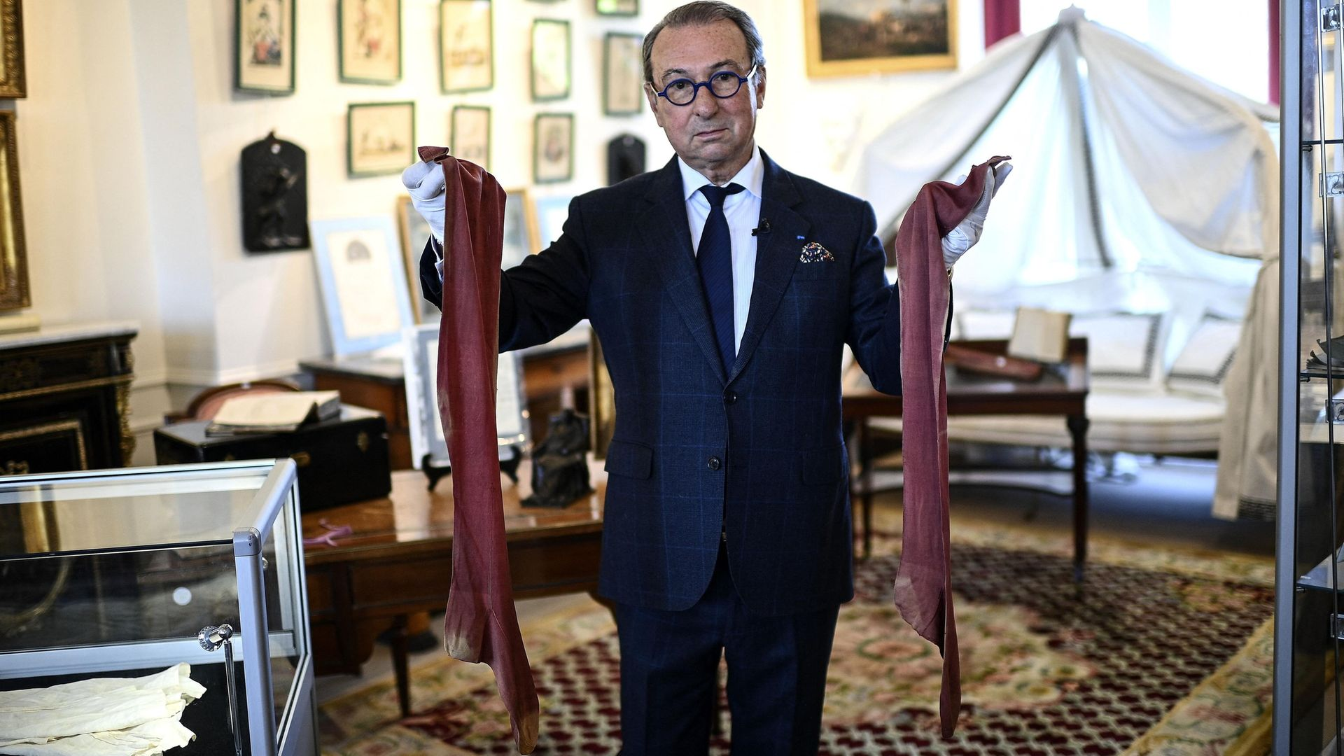 Auctioneer Jean-Pierre Osenat holds a pair of stockings that belonged to Napoleon - Credit: Photo by CHRISTOPHE ARCHAMBAULT/AFP via Getty Images