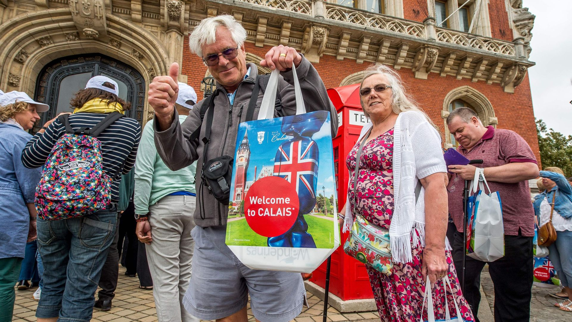 A British tourist poses with a shopping bag at Calais Town Hall - Credit: Photo: PhilippeHuguen/AFP via Getty Images