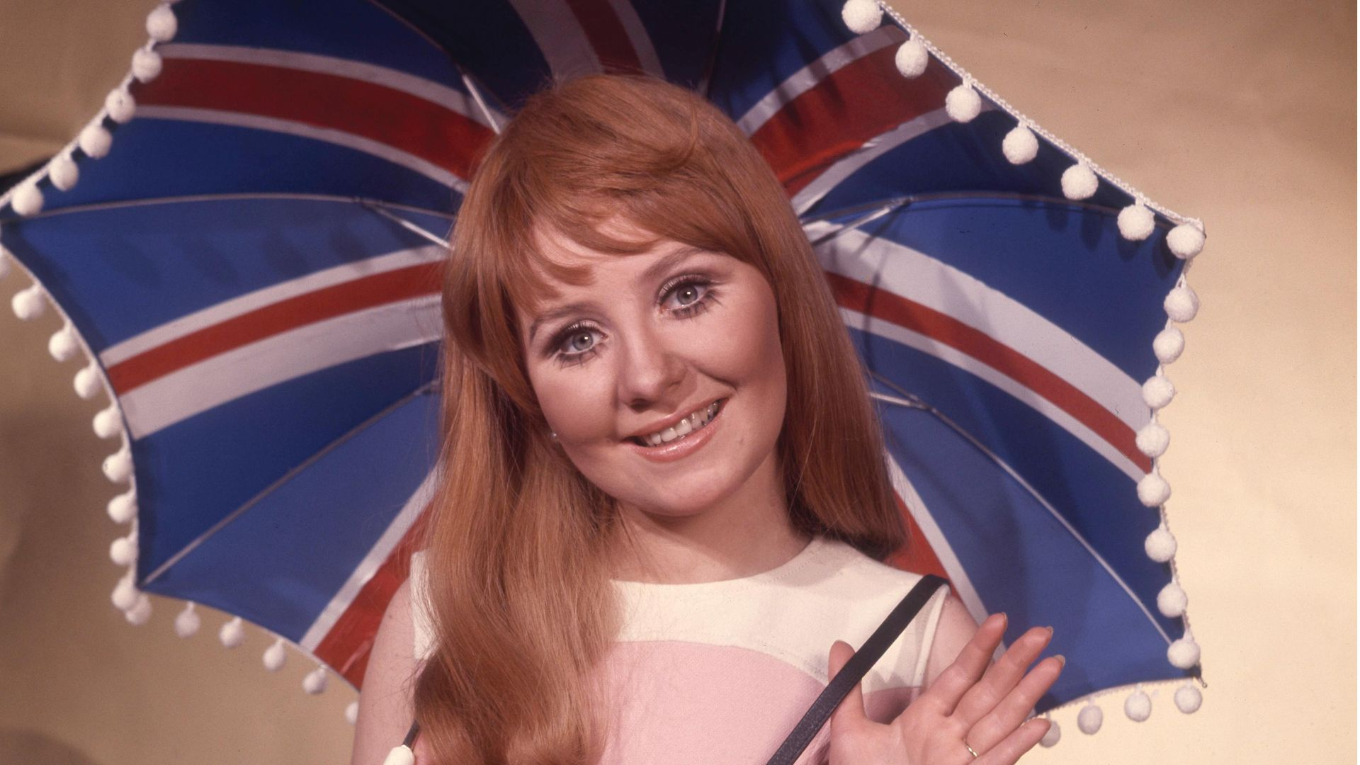 """British singer Lulu holding Union Jack umbrella as she represents the UK in the 1969 Eurovision Song Contest with song """"Boom Bang-a-Bang"""" - Credit: Getty Images"""