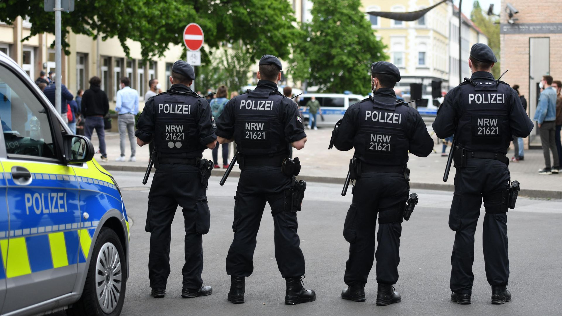 """Policemen stand in front of a synagogue in Gelsenkirchen, Germany. Officials vowed """"unwavering"""" protection of synagogues after scattered demonstrations over the conflict in the Middle East saw protesters shout anti-Israeli slogans and burn Israeli flags - Credit: AFP via Getty Images"""