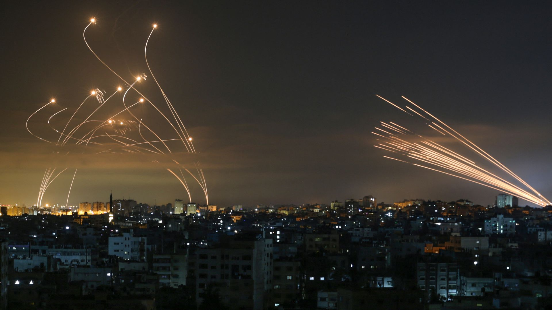 The Israeli Iron Dome missile defence system (left) intercepts rockets (right) fired by Hamas towards southern Israel from Beit Lahia in the northern Gaza Strip - Credit: AFP via Getty Images