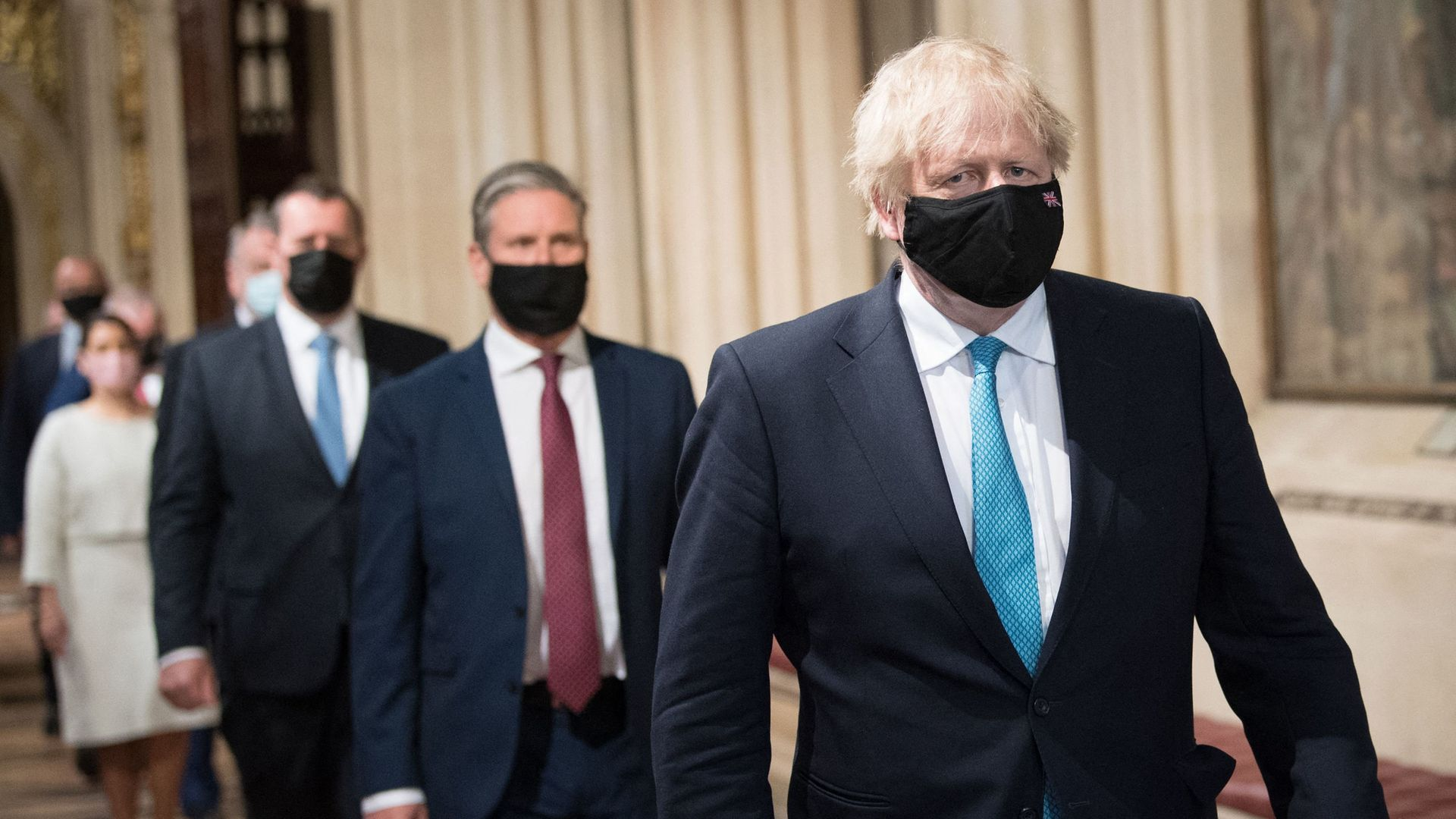 Prime Minister Boris Johnson (R) and opposition leader Keir Starmer (C), both wearing face coverings, walk in a socially distanced single file line through the Central Lobby after listening to the Queen's Speech - Credit: POOL/AFP via Getty Images