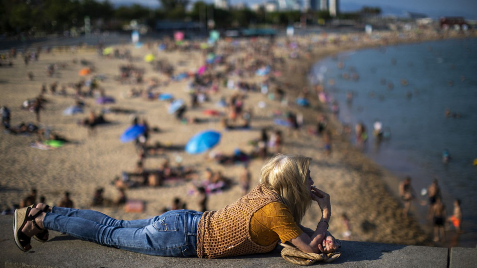 A woman smokes lying on a wall as people enjoy the beach in Barcelona, Spain - Credit: AP