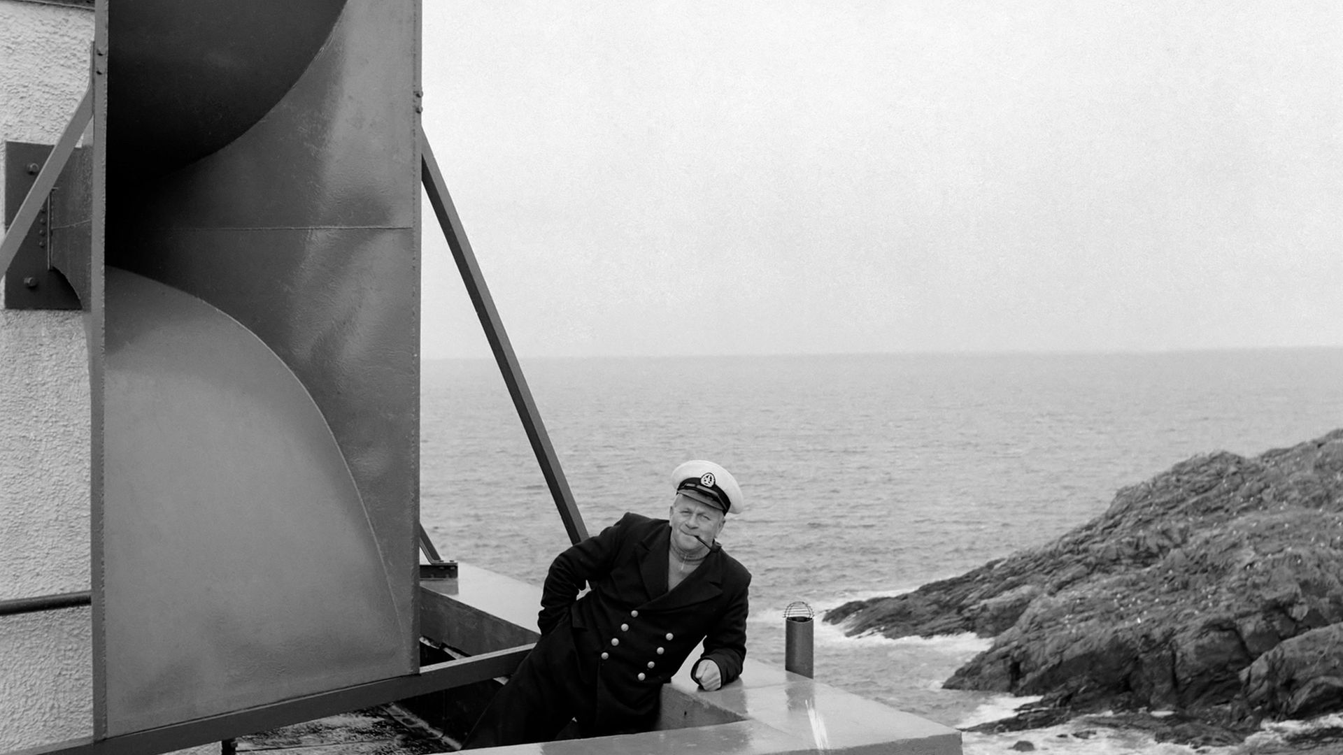 A lighthouse keeper at Strathy Point, on the north coast of Scotland, poses in front of the site's vast foghorn, in 1960 - Credit: Mirrorpix via Getty Images