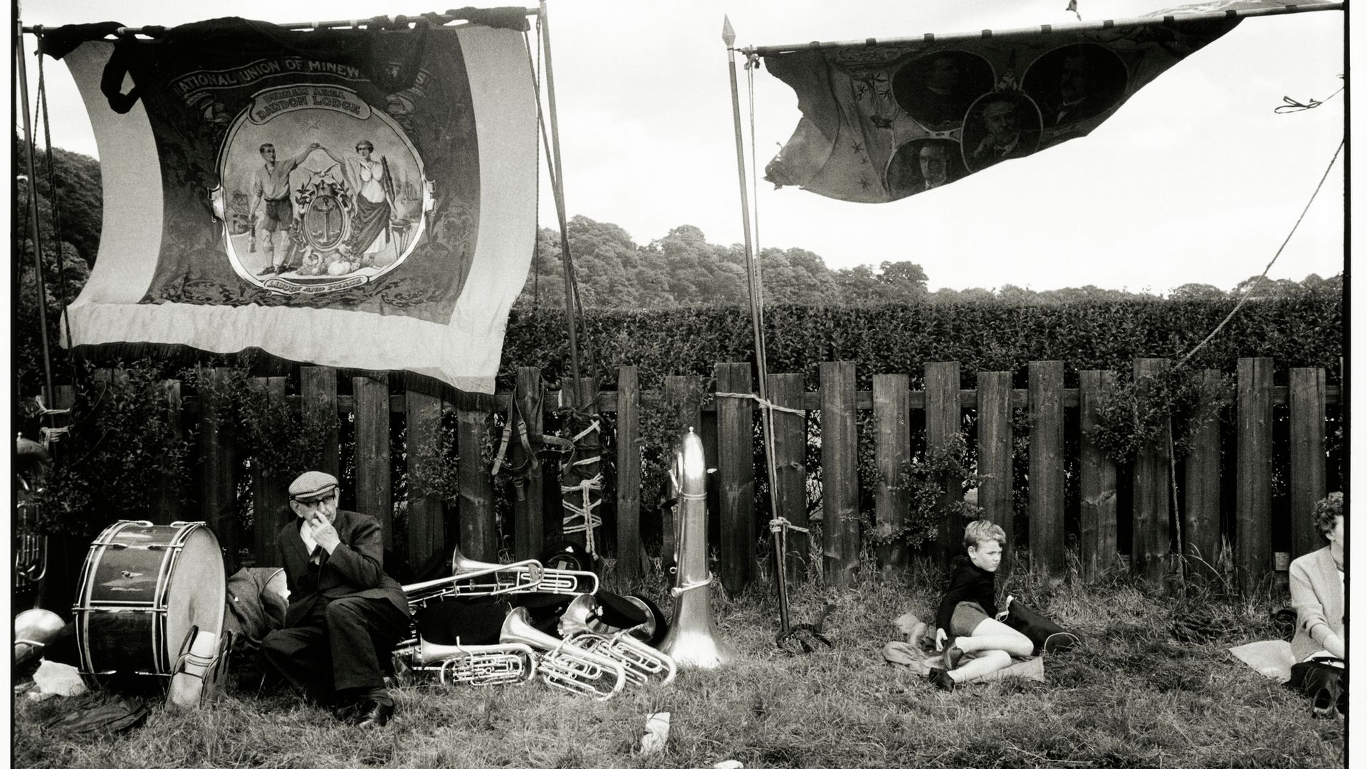 Trade union banners fly as people rest amid musical instruments during the 1969 Durham Miners' Gala, a major union gathering. The image was taken by Tony Ray-Jones, a photographer known for capturing the unguarded moments of people from all sections of British society - Credit: SSPL via Getty Images