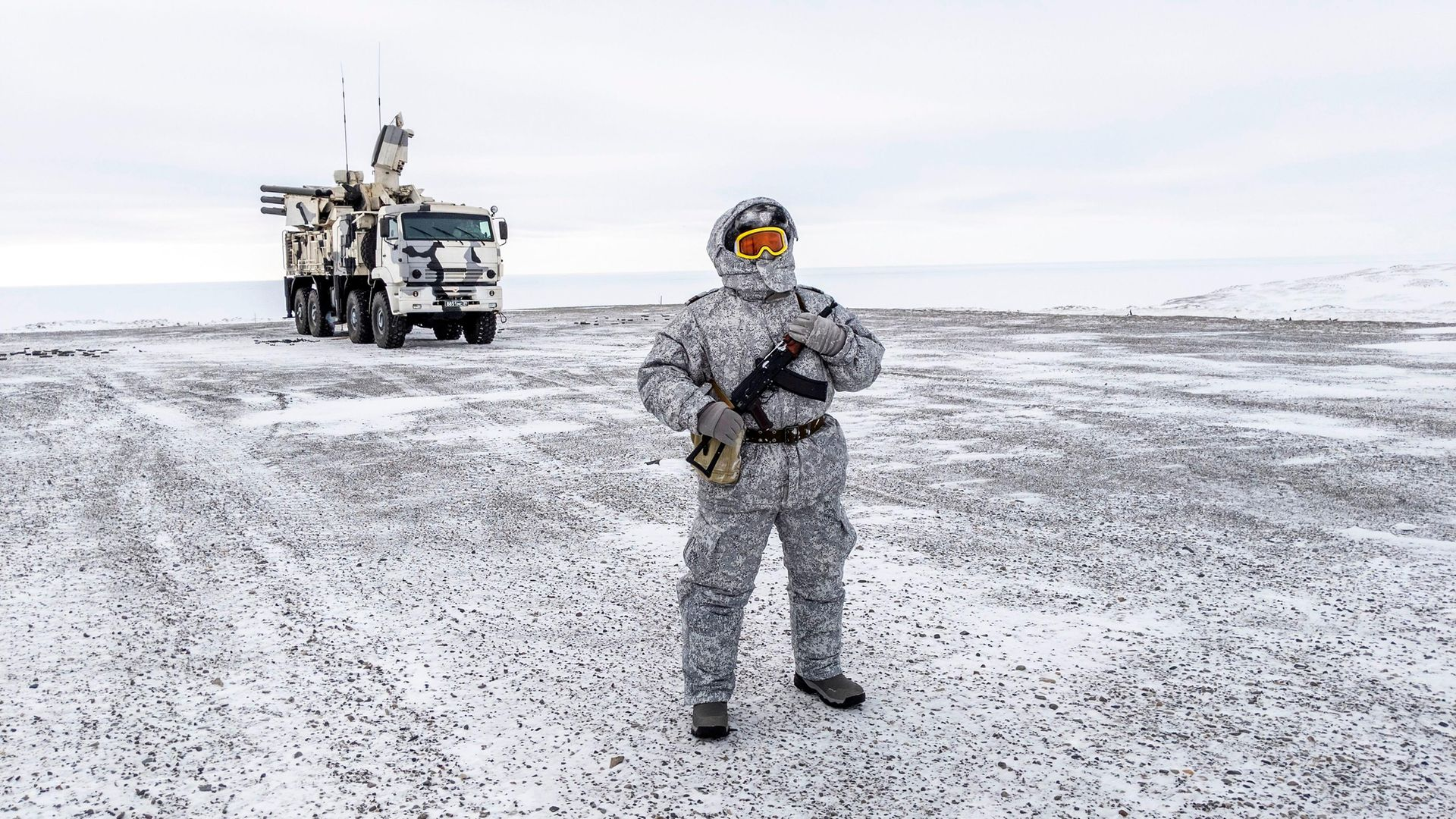 A soldier holds a machine gun as he patrols the Russian northern military base on Kotelny island, beyond the Artic circle - Credit: AFP via Getty Images