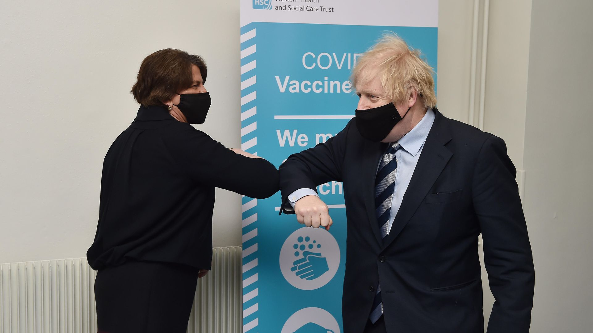 Prime Minister Boris Johnson is greeted with an elbow bump by First Minister Arlene Foster during a visit to Northern Ireland - Credit: PA