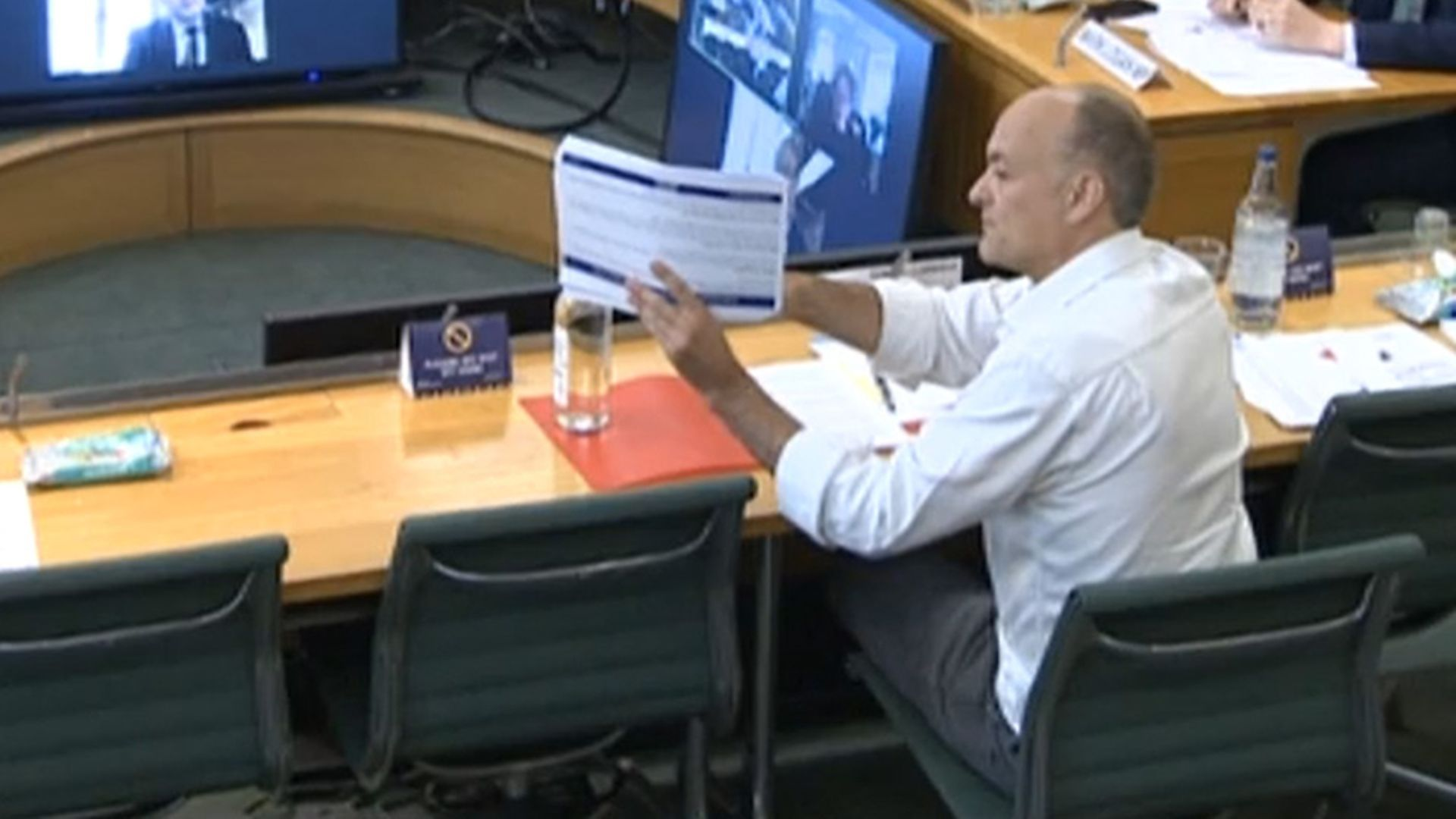 Dominic Cummings, former Chief Adviser to Prime Minister Boris Johnson, holds up a document whilst giving evidence to a joint inquiry of the Commons Health and Social Care and Science and Technology Committees - Credit: PA