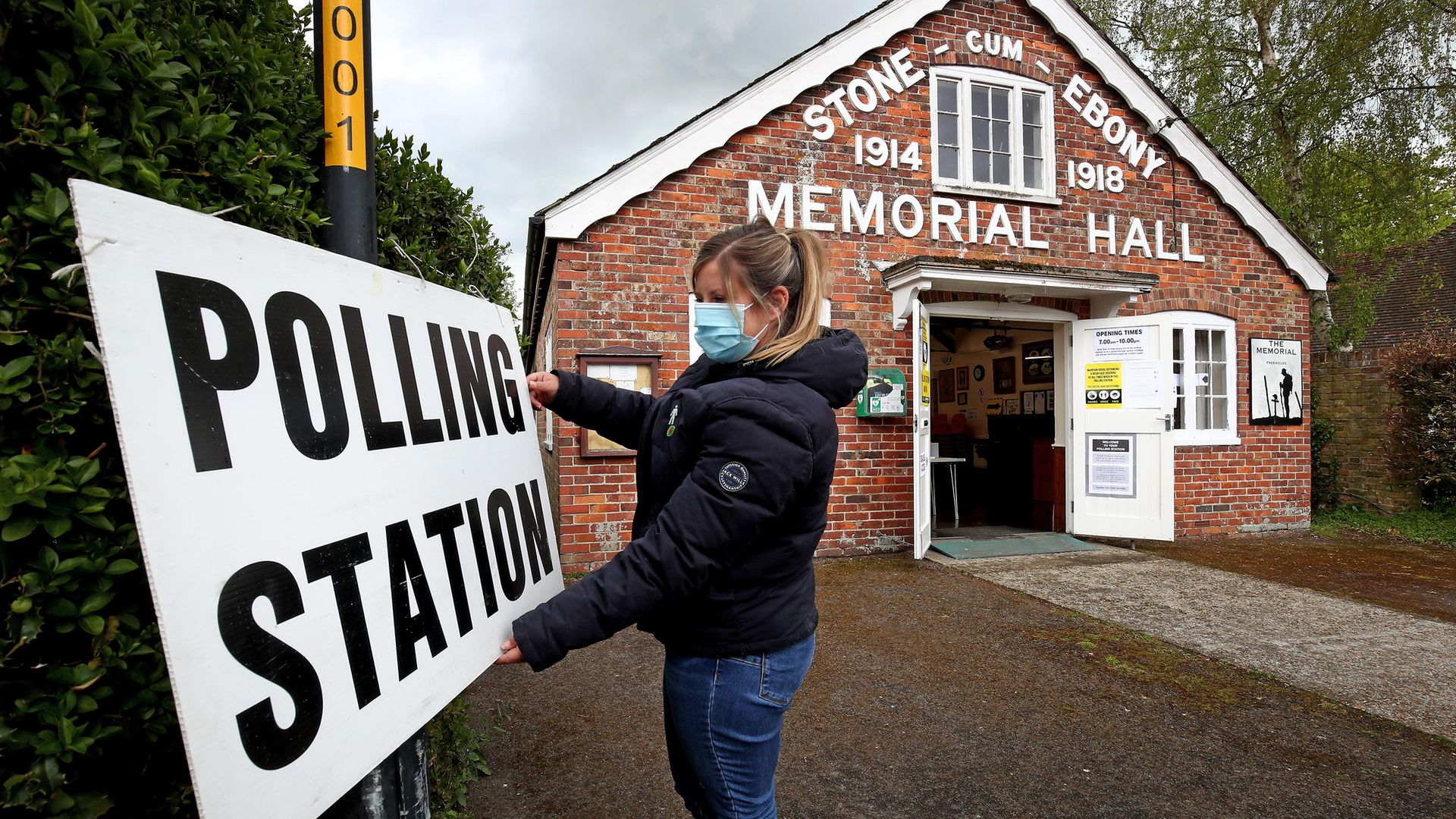A poll clerk adjusts the sign outside a polling station - Credit: PA
