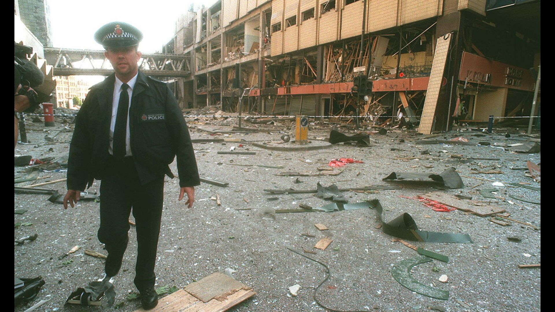 A police officer amid the damage caused by the IRA bomb in Manchester city centre - Credit: Sygma via Getty Images