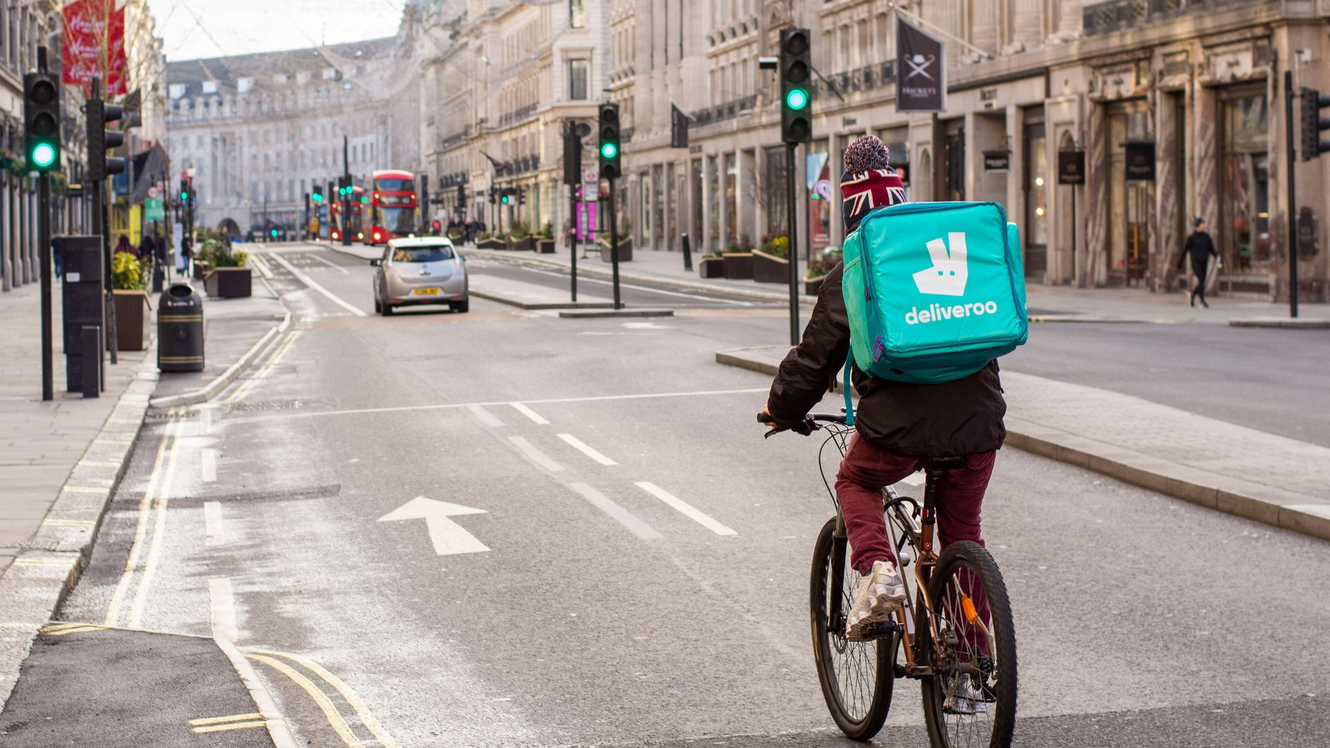 A Deliveroo courier rides along London's empty Regent Street during the Covid-19 lockdown - Credit: Photo by Pietro Recchia/SOPA Images/LightRocket via Getty Images