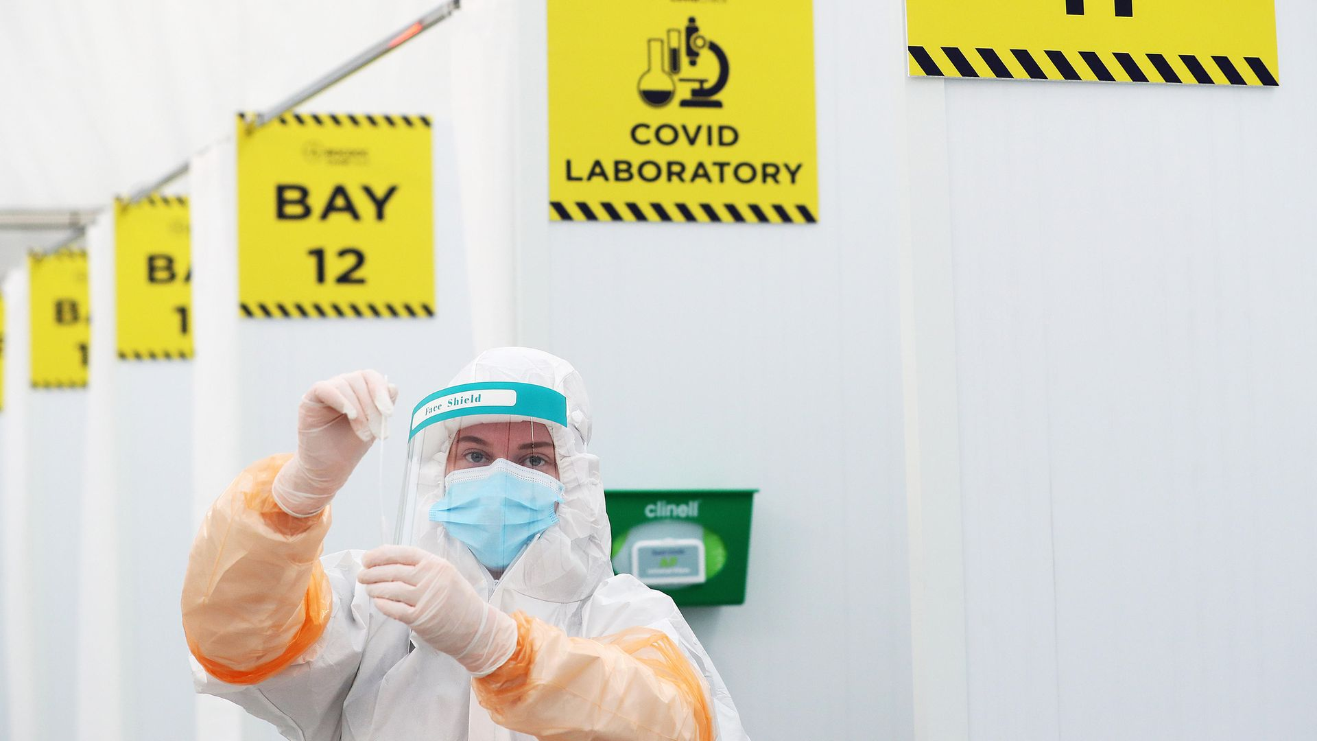 A lab technician with a swab at a testing facility at Dublin Airport - Credit: PA