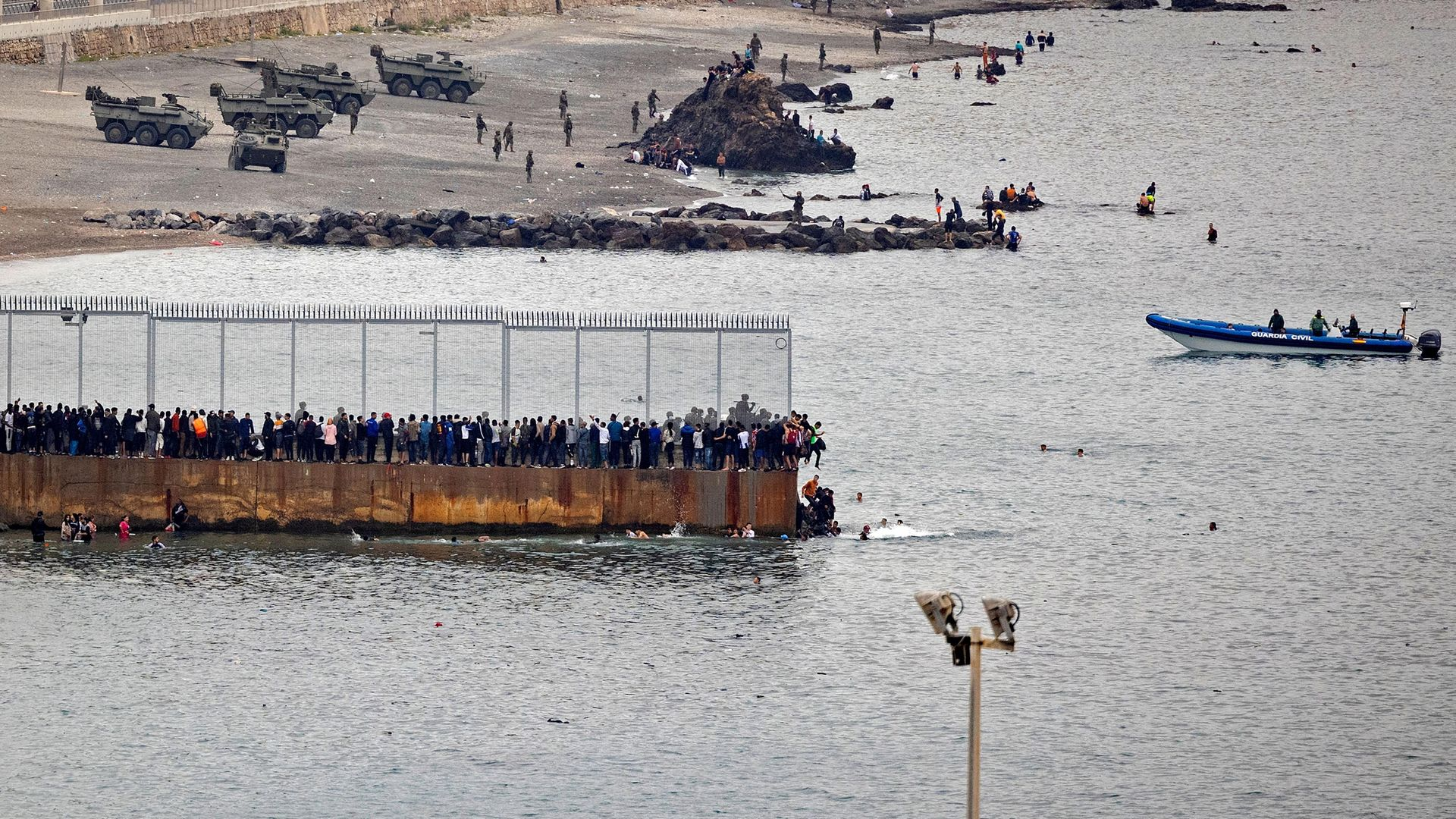 Migrants rally by a border fence to cross from Morocco to Spain's North African enclave of Ceuta, where Spanish troops await - Credit: AFP via Getty Images