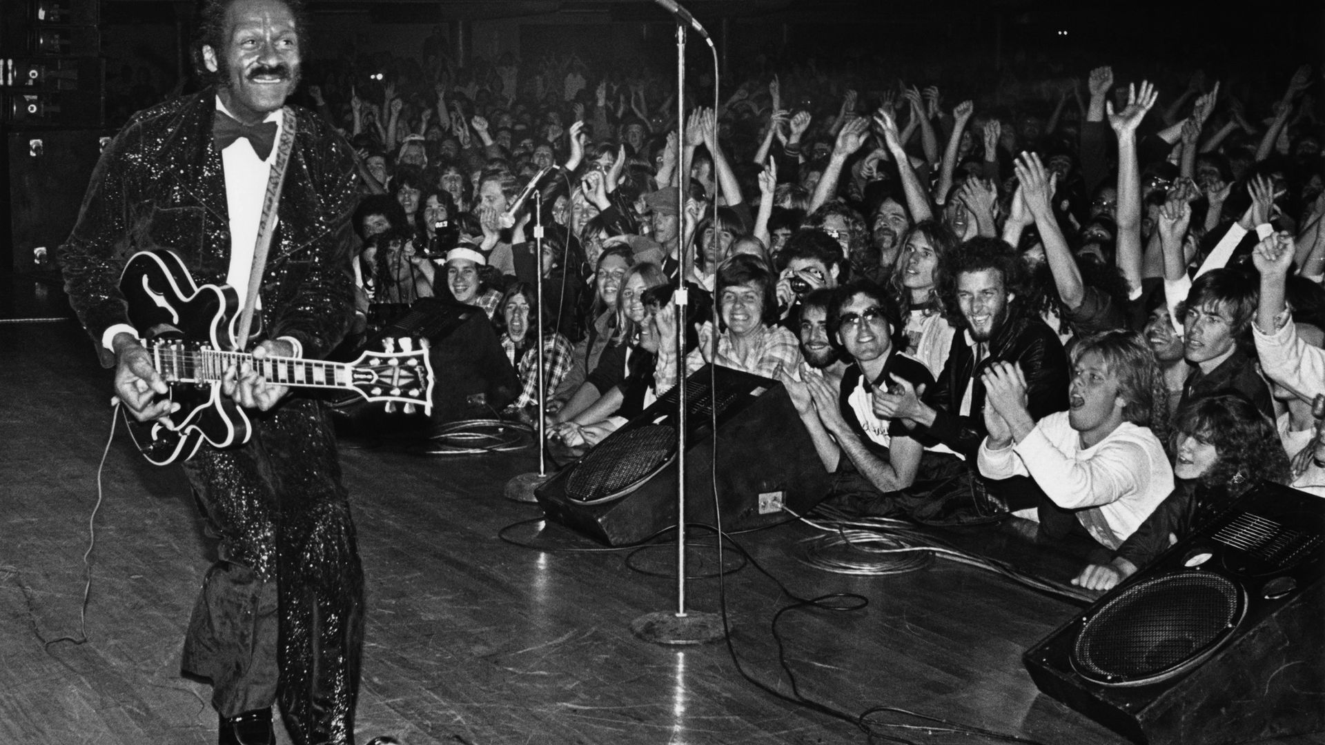 """Chuck Berry struts his signature """"duck walk"""" while playing his Gibson guitar, to the delight of fans, during a 1980 Hollywood, California, concert at the Palladium - Credit: Getty Images"""