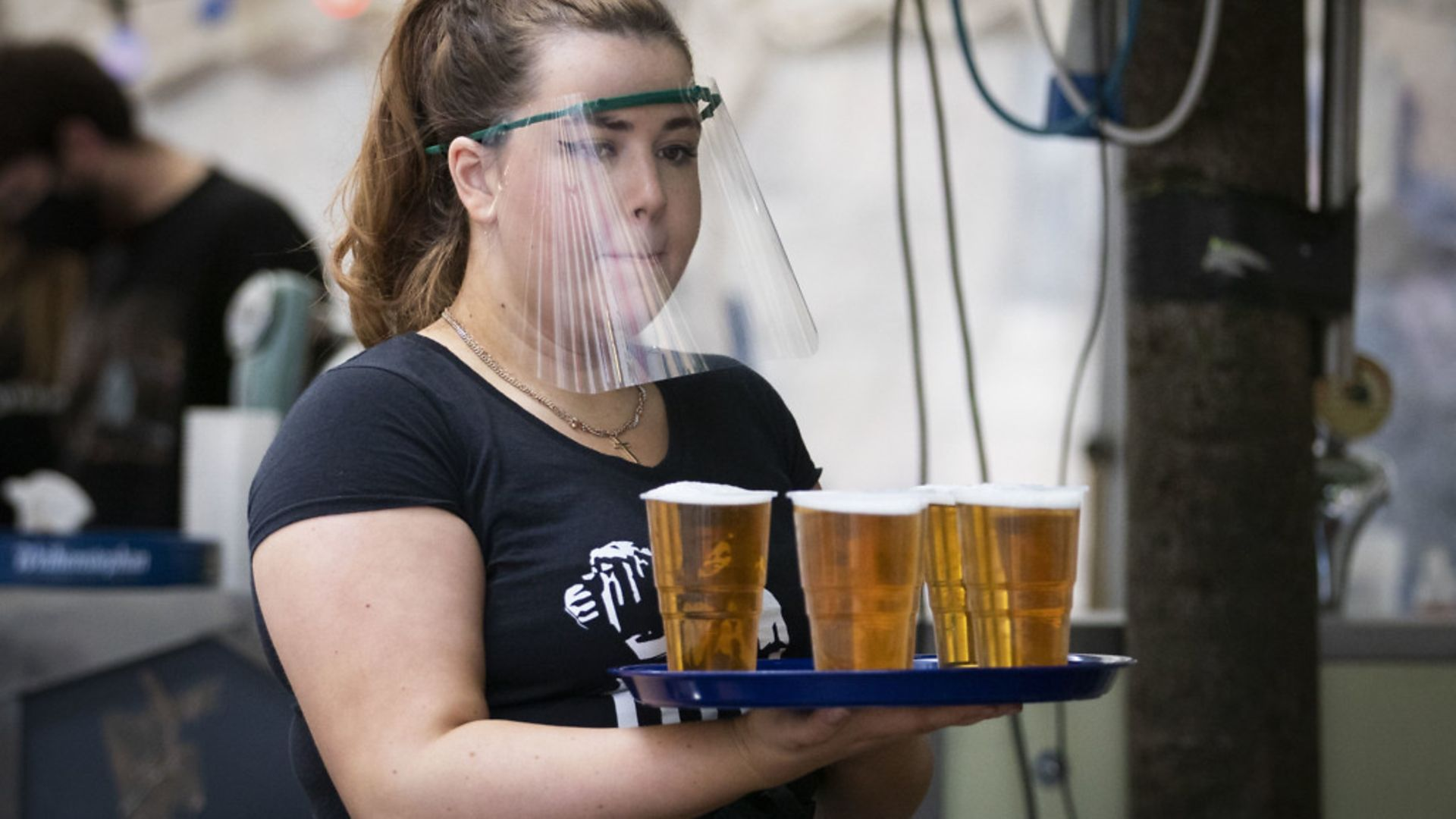 A member of staff serves drinks in a beer garden at a UK pub as they start to reopen - Credit: PA