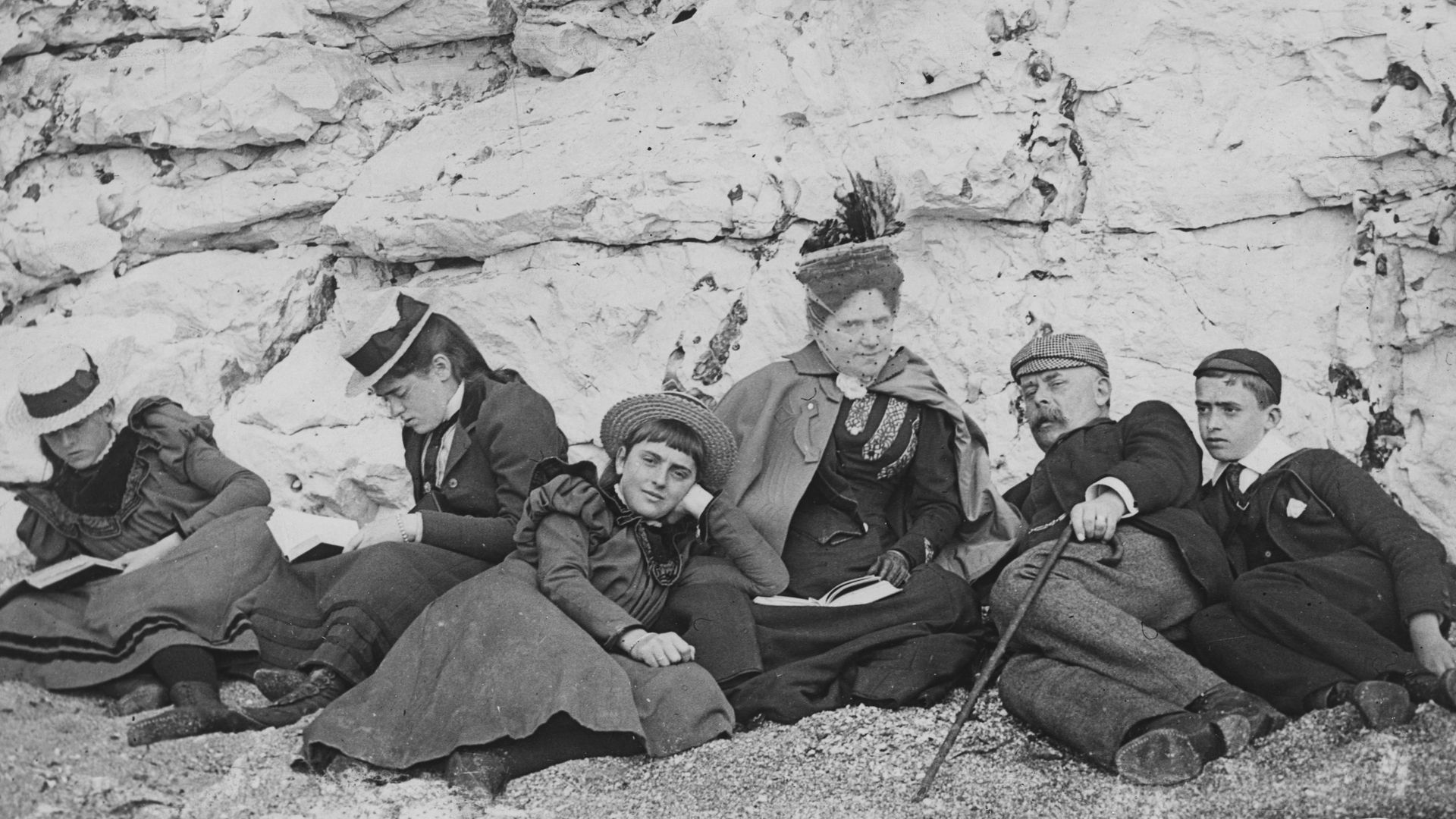 A group of holiday-makers sunning themselves on a south coast beach in 1895. Three of them have their noses in books - Credit: Express/Express/Getty Images