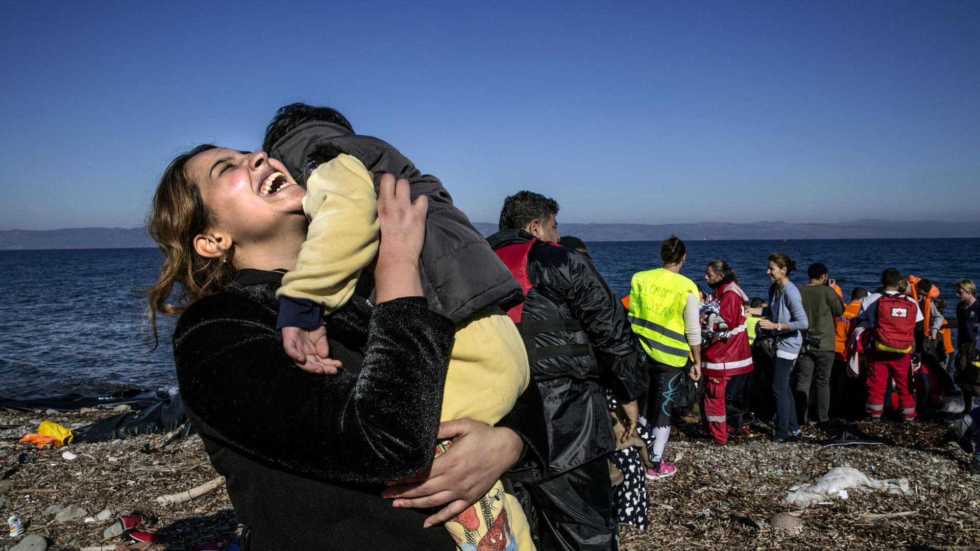 A Syrian refugee rejoices after arriving on an overcrowded raft to the island of Lesbos, Greece, in 2015 - Credit: Getty Images