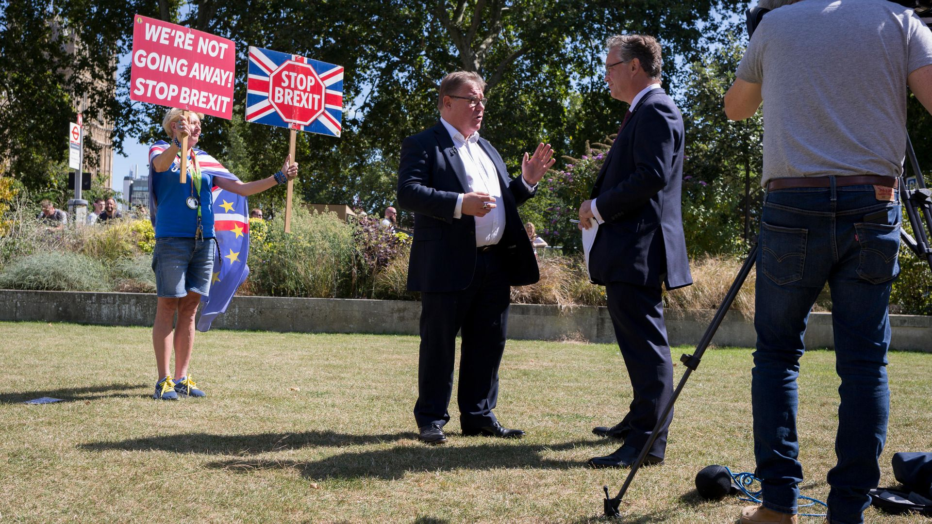 As a Remain protestor holds up placards behind him, Brexiteer MP Mark Francois is interviewed on College Green in August 2019 - Credit: In Pictures via Getty Images