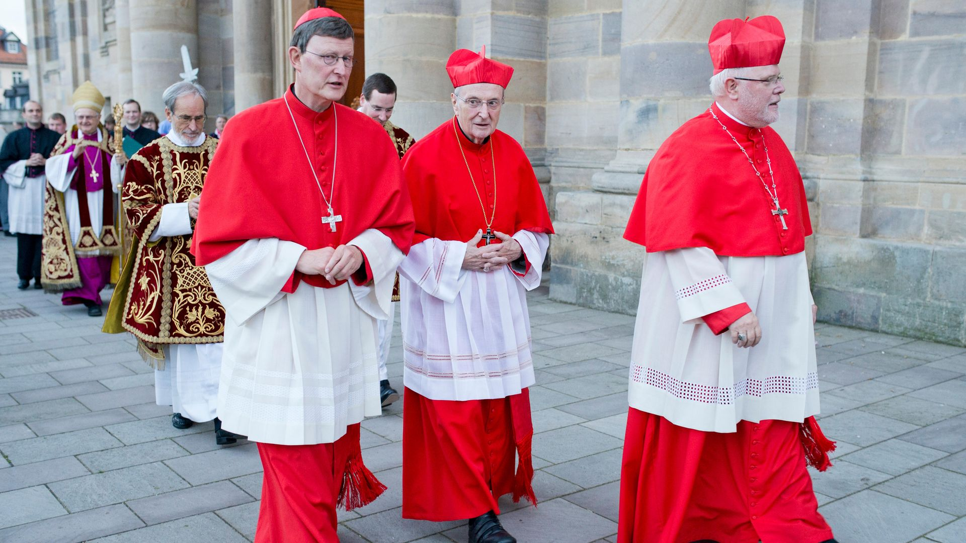 TALE OF TWO CARDINALS: Rainer Maria Woelki (left) and Reinhard Marx (right), with a third cardinal, Joachim Meisner, in between, in Fulda, Germany, in 2013 - Credit: Photothek via Getty Images
