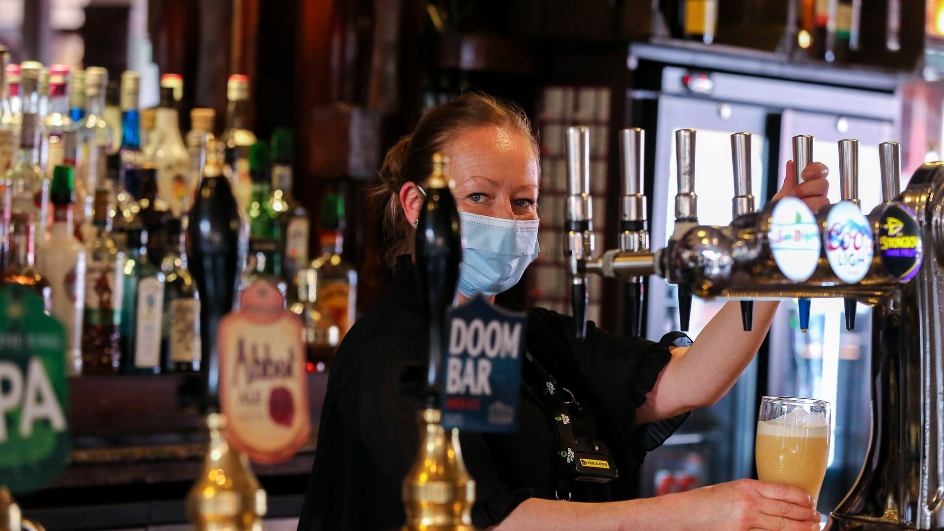 A bar worker pulls a pint for a customer; many pubs are facing a staff shortage - Credit: Dinendra Haria/SOPA Images/LightRocket via Getty