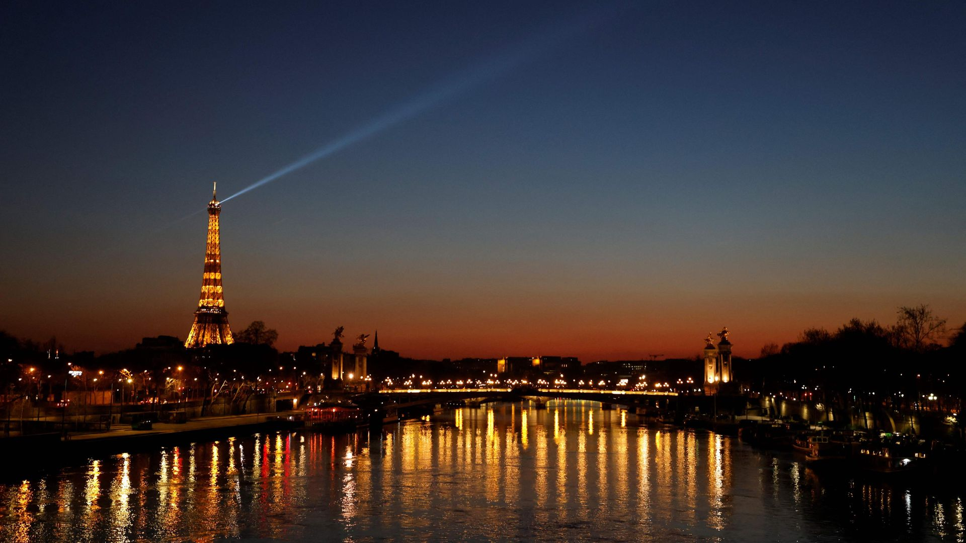 A spotlight shines from the Eiffel Tower at sunset, in March 2021 - Credit: AFP via Getty Images