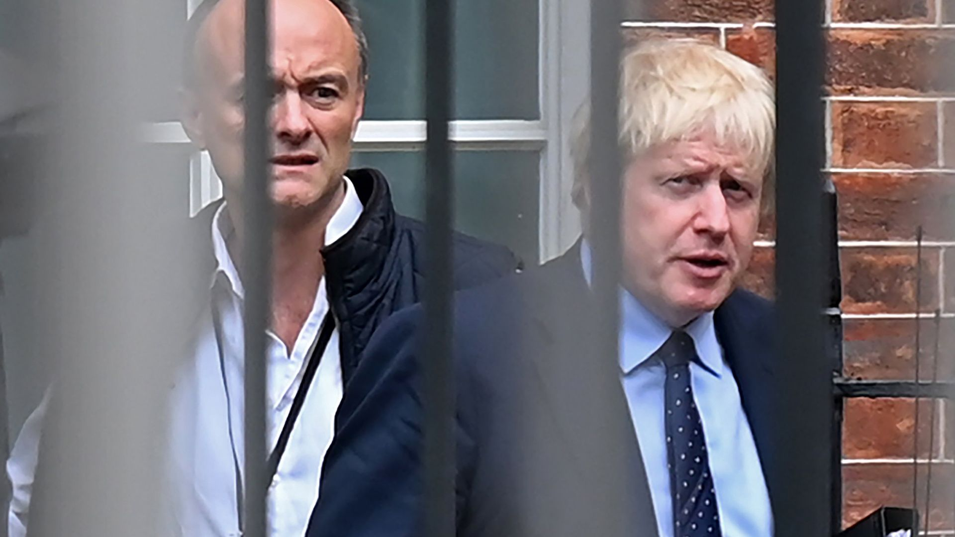 Britain's Prime Minister Boris Johnson (R) and former special advisor Dominic Cummings leave from the rear of Downing Street - Credit: AFP via Getty Images