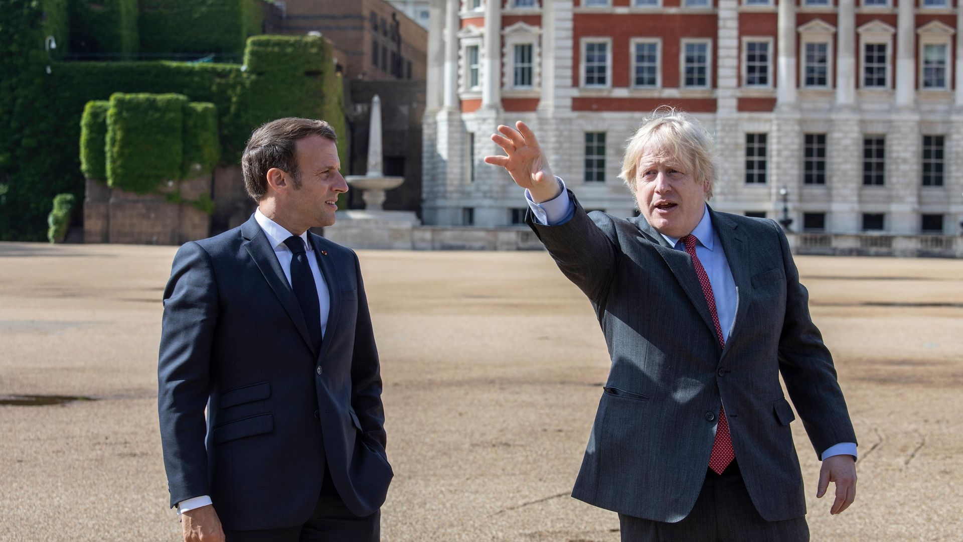 Prime minister Boris Johnson (right) and French president Emmanuel Macron watch a flypast of the Red Arrows and their French equivalent, La Patrouille de France from Horse Guards Parade in London during his visit to the UK - Credit: PA